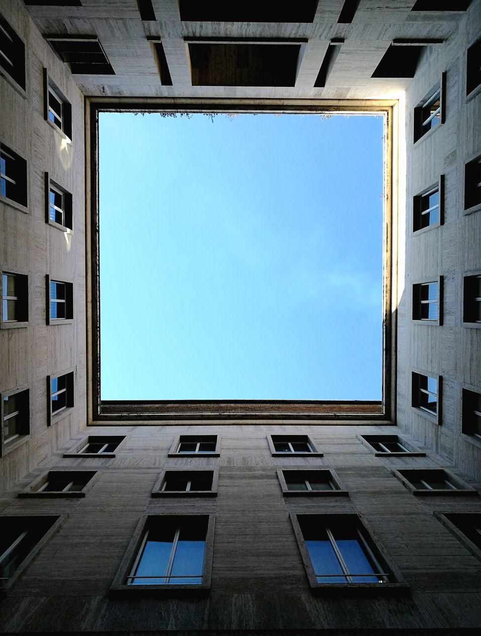 architecture, window, building exterior, built structure, low angle view, sky, blue, day, no people, sunlight, outdoors, city