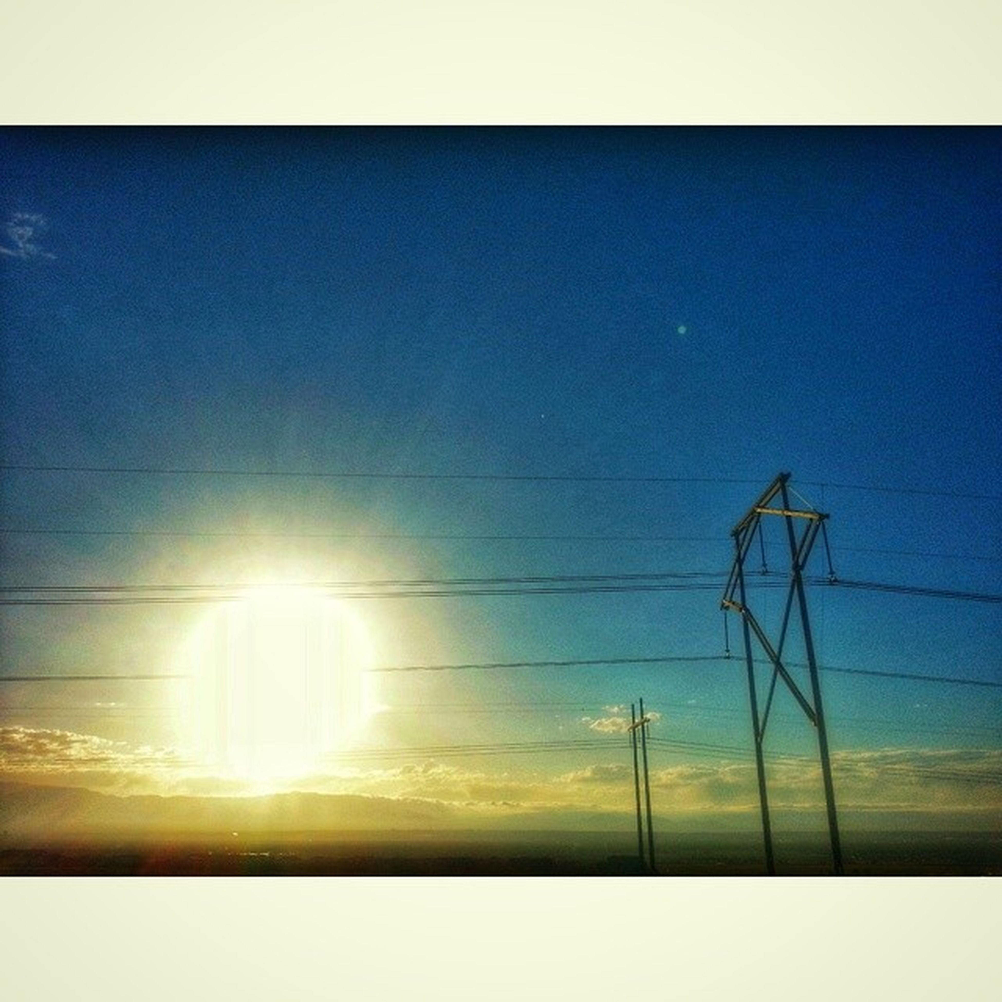 transfer print, sun, sky, auto post production filter, power line, tranquility, sunlight, sunset, scenics, tranquil scene, beauty in nature, low angle view, electricity pylon, nature, blue, sunbeam, electricity, power supply, outdoors, lens flare