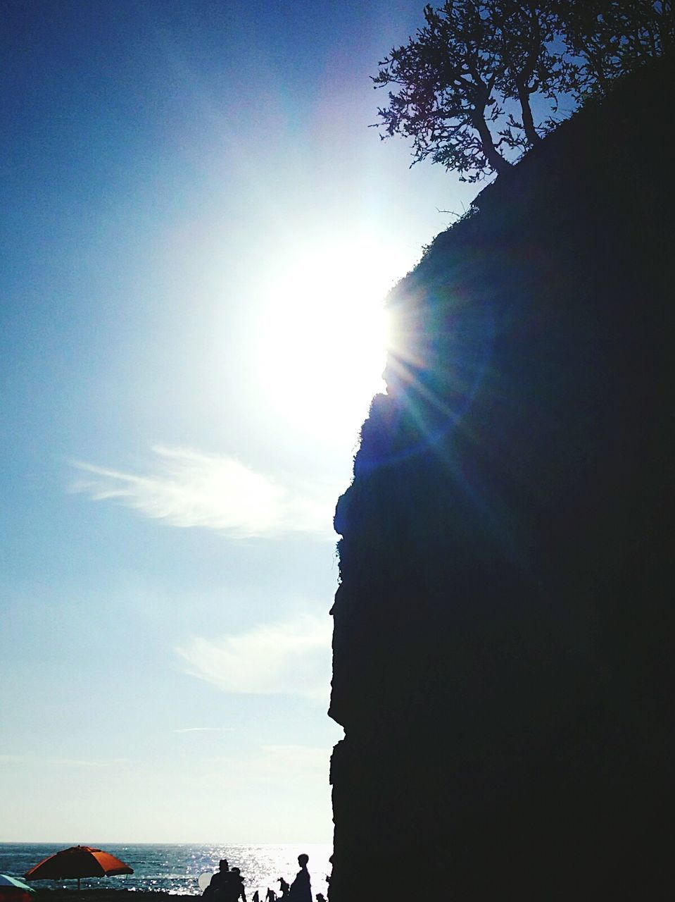 Silhouette Cliff By Sea Against Sky On Sunny Day