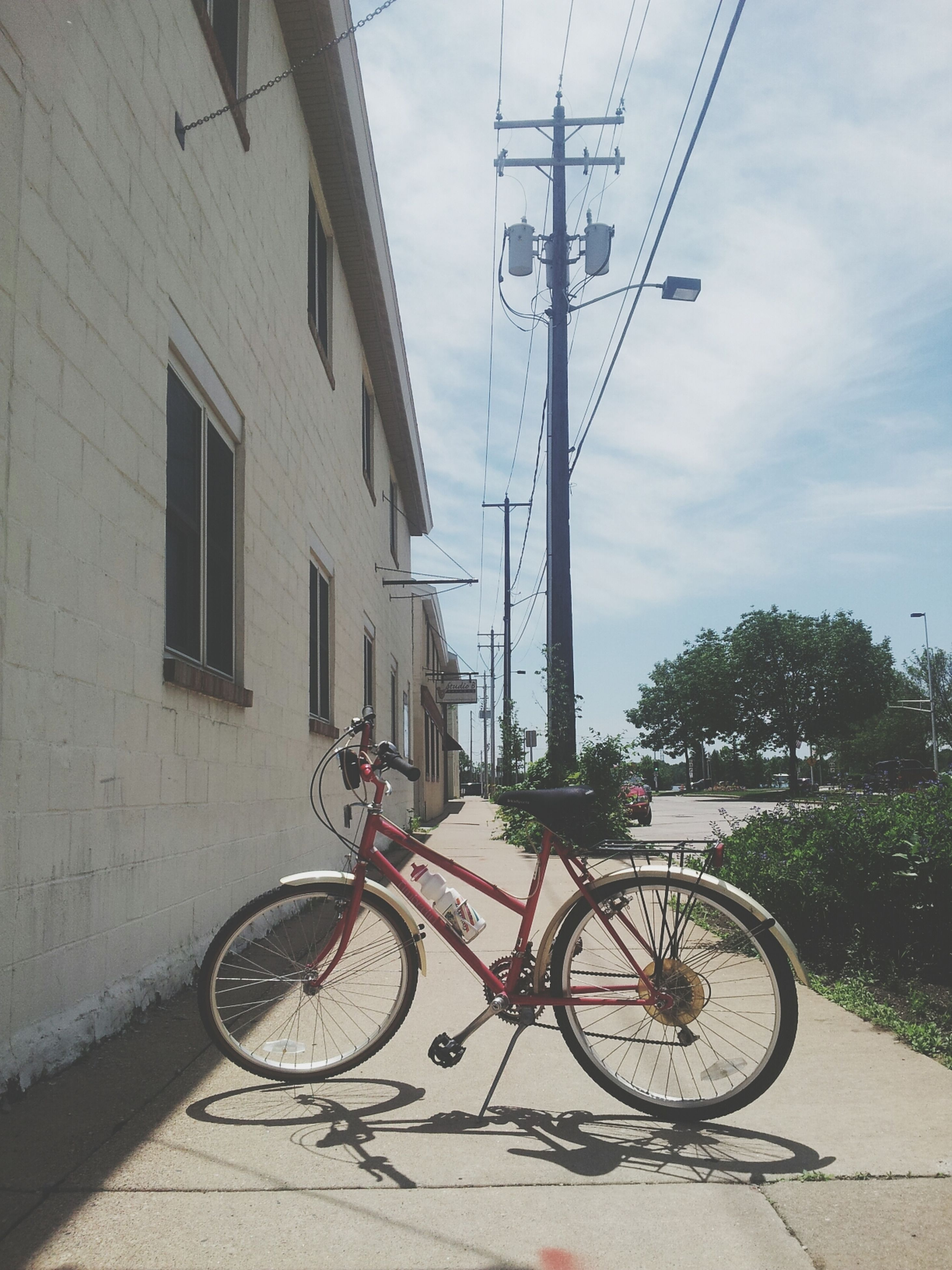 bicycle, transportation, mode of transport, architecture, building exterior, built structure, land vehicle, stationary, parked, power line, sky, parking, street, cable, day, outdoors, road, sunlight, electricity pylon, tree