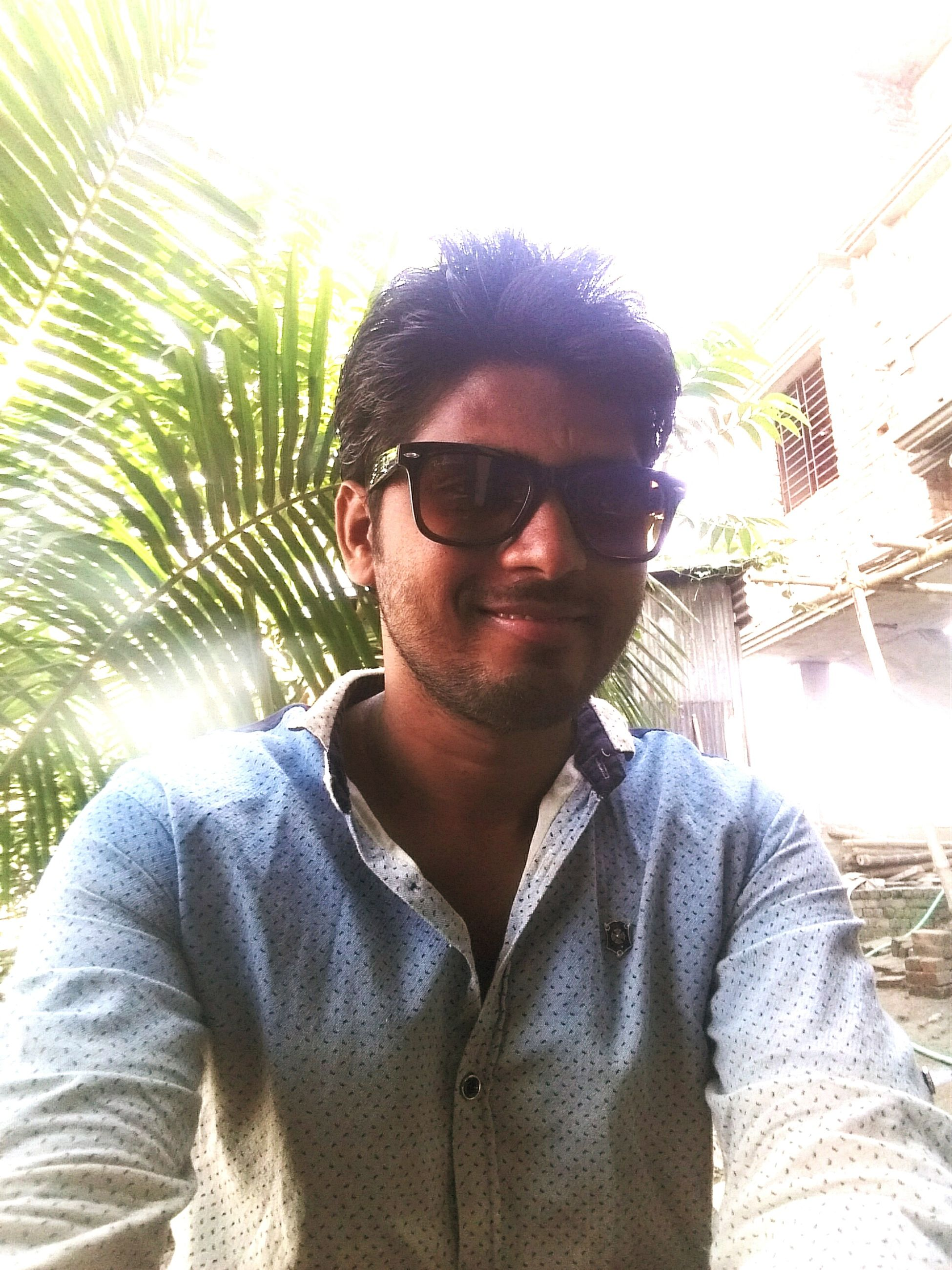 sunglasses, lifestyles, portrait, sunlight, young adult, lens flare, casual clothing, looking at camera, front view, one person, one young man only, outdoors, leisure activity, confidence, tree, day, happiness, smiling, real people, adults only, only men, close-up, adult, one man only, nature, people, sky, trendy