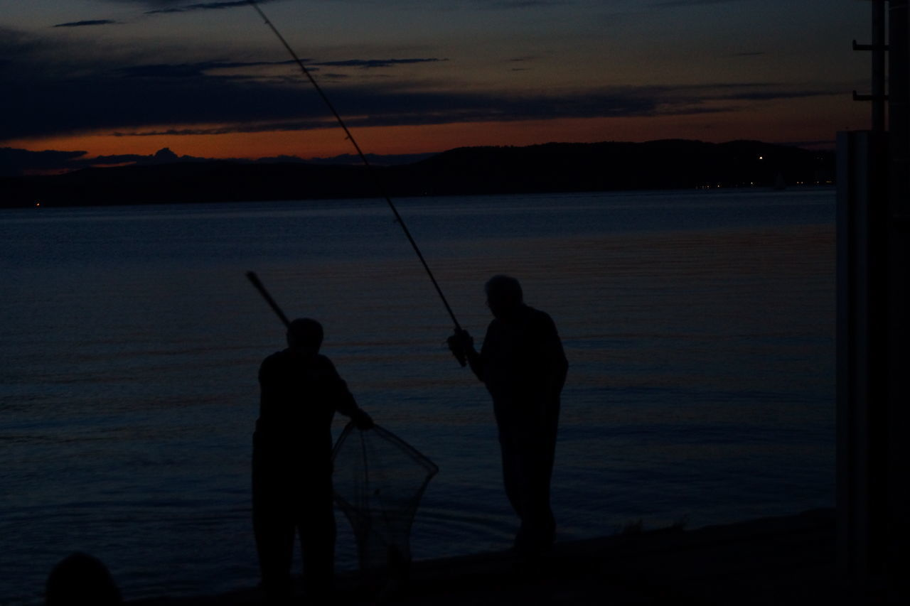 fishing, fishing rod, silhouette, real people, fishing pole, standing, nature, two people, men, water, sea, leisure activity, weekend activities, holding, sunset, fisherman, beauty in nature, fishing tackle, togetherness, outdoors, sky, full length, fishing equipment, scenics, horizon over water, day