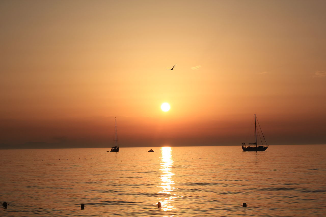 Silhouette Of Boats In Sea During Sunset