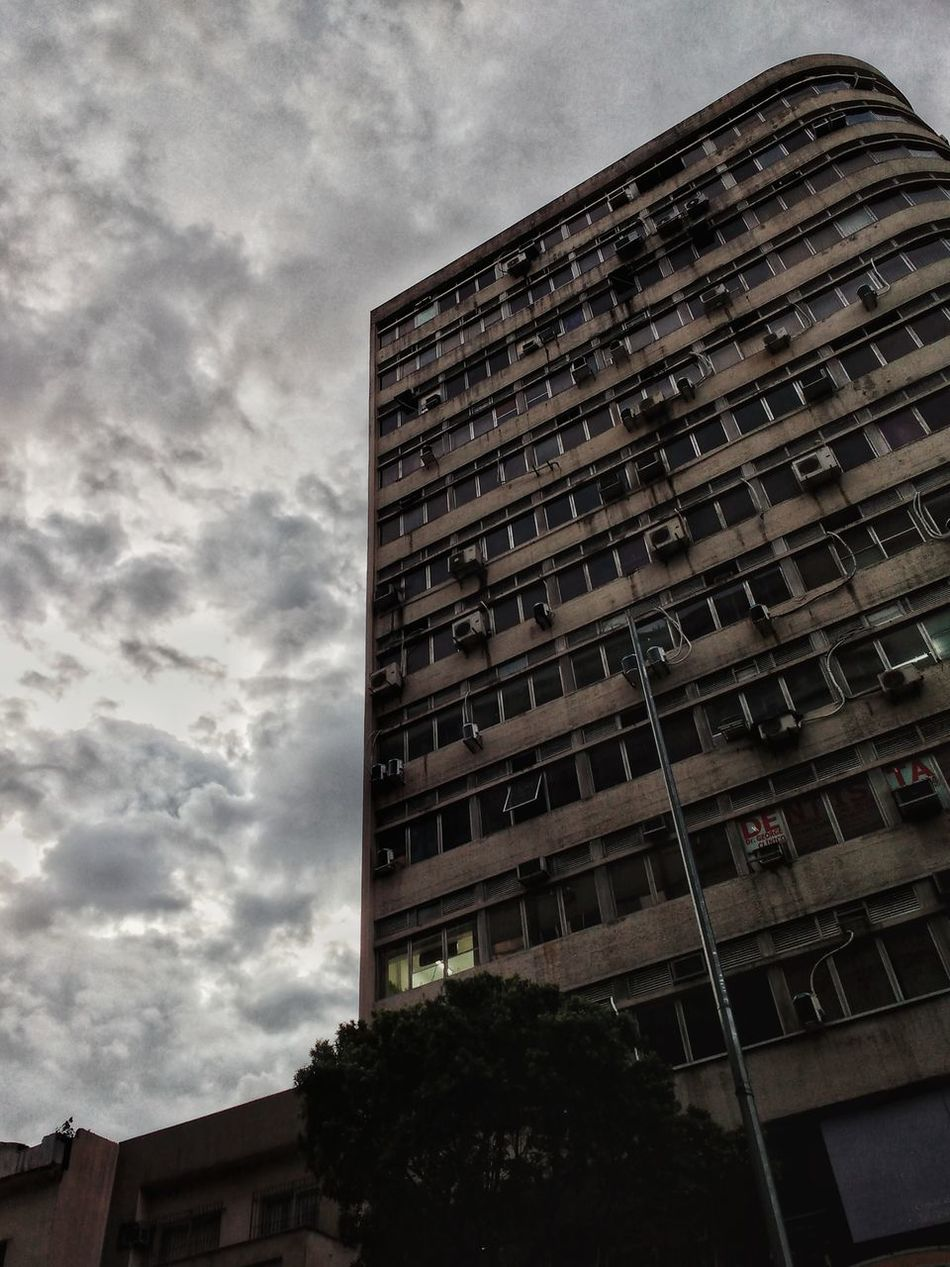 An old and run down commercial and residential apartment block contrasts with a grey cloudy sky. Building Exterior Architecture Built Structure Low Angle View Sky Outdoors City No People Cloud - Sky Growth Tree Skyscraper Day HDR Brazilian Apartment Block Third World Country Developing Country Residential Building Commercial Building Run Down Derelict Contrast Cloudy Sky Grey