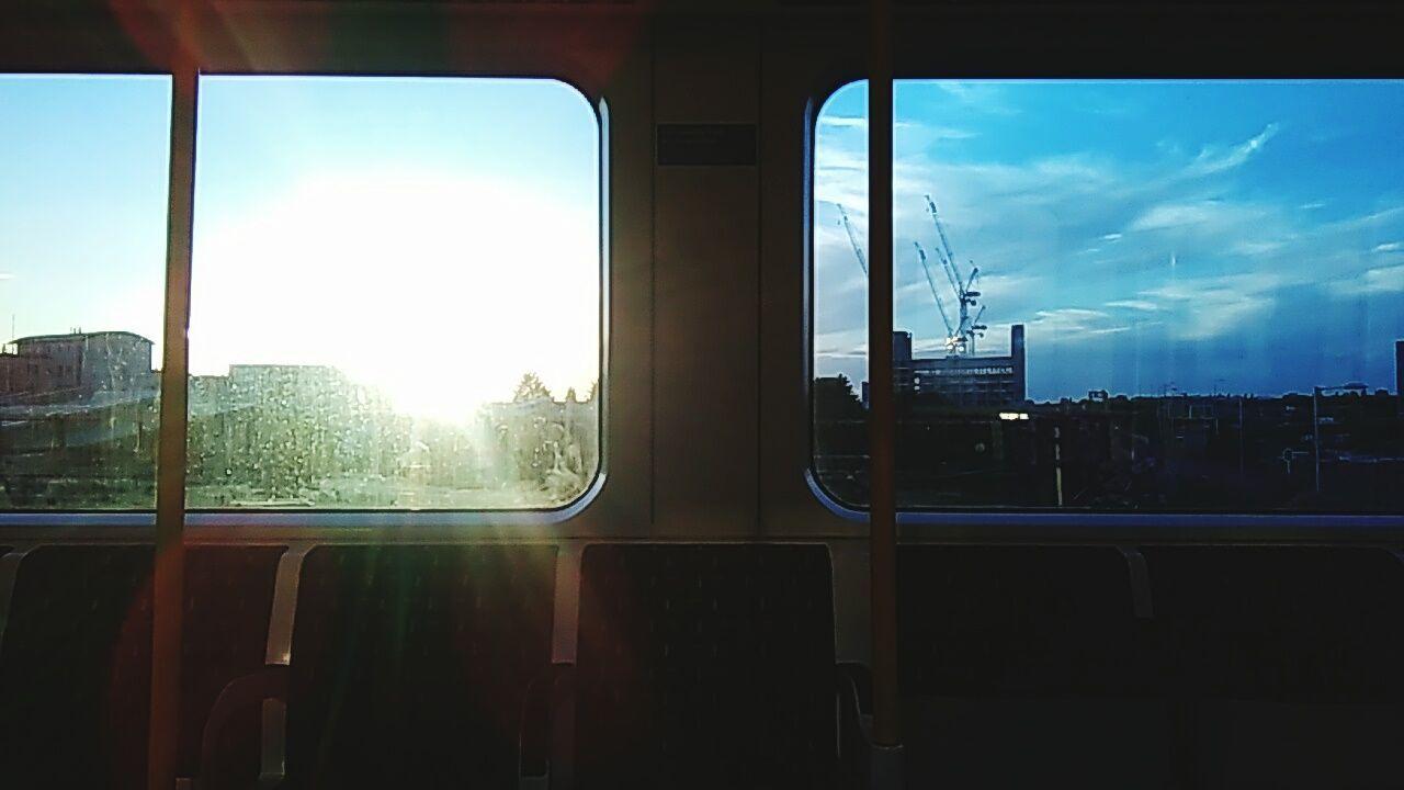 window, transportation, vehicle interior, sky, train - vehicle, mode of transport, public transportation, rail transportation, travel, day, cloud - sky, sunlight, no people, indoors, city, nature