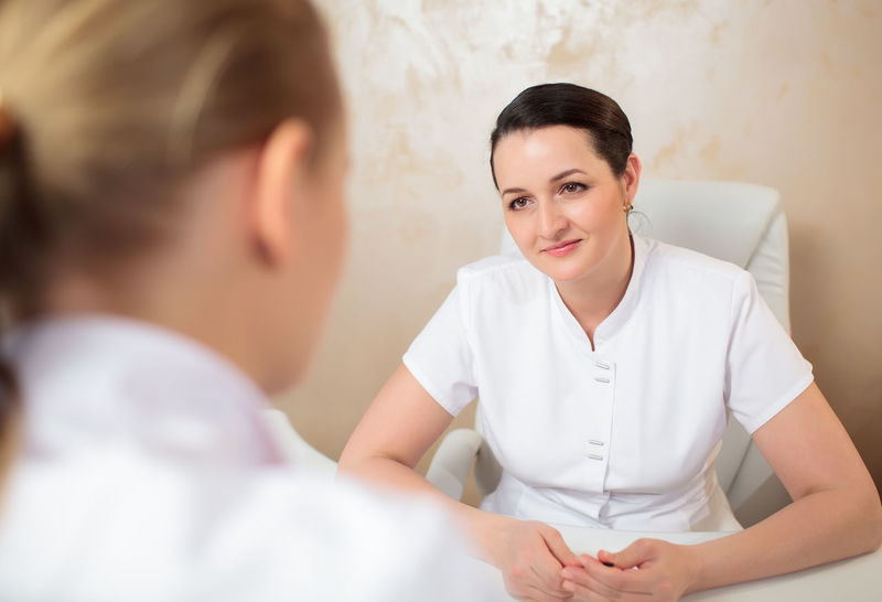 Armchair Beautician Caucasian Colleague Cosmetician Discussion Doctor  Explain Indoor Medical Office Profession Room Specialist Tablet Talk Touch Pad Touchpad Two Woman