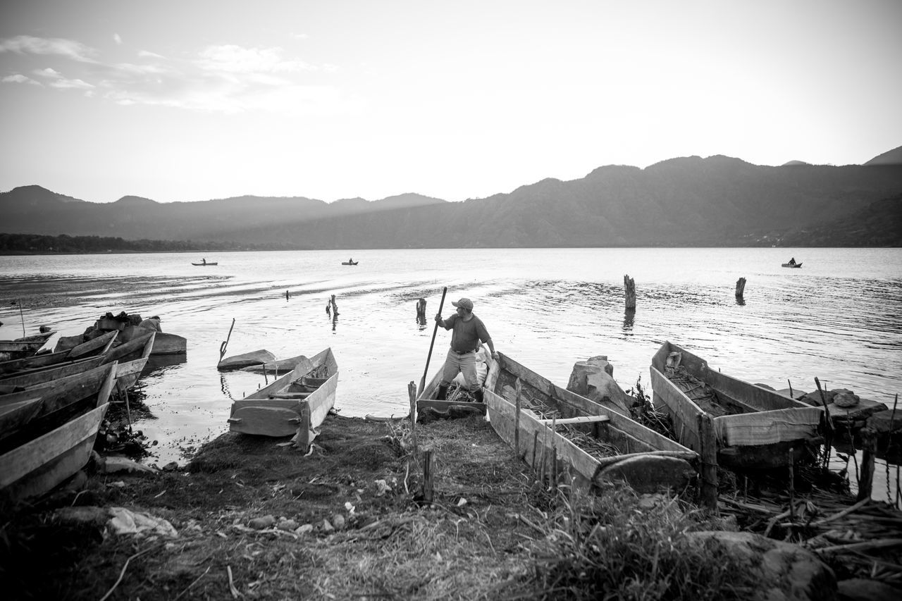 Fishing boats on Lake Atitlán, Santiago Atitlán, Guatemala. Adult Beach Beauty In Nature Day Fisherman Fishing Guatemala Lake Atitlan Guatemala Lake Atitlán Men One Person Outdoors People Real People Tranquil Scene Water