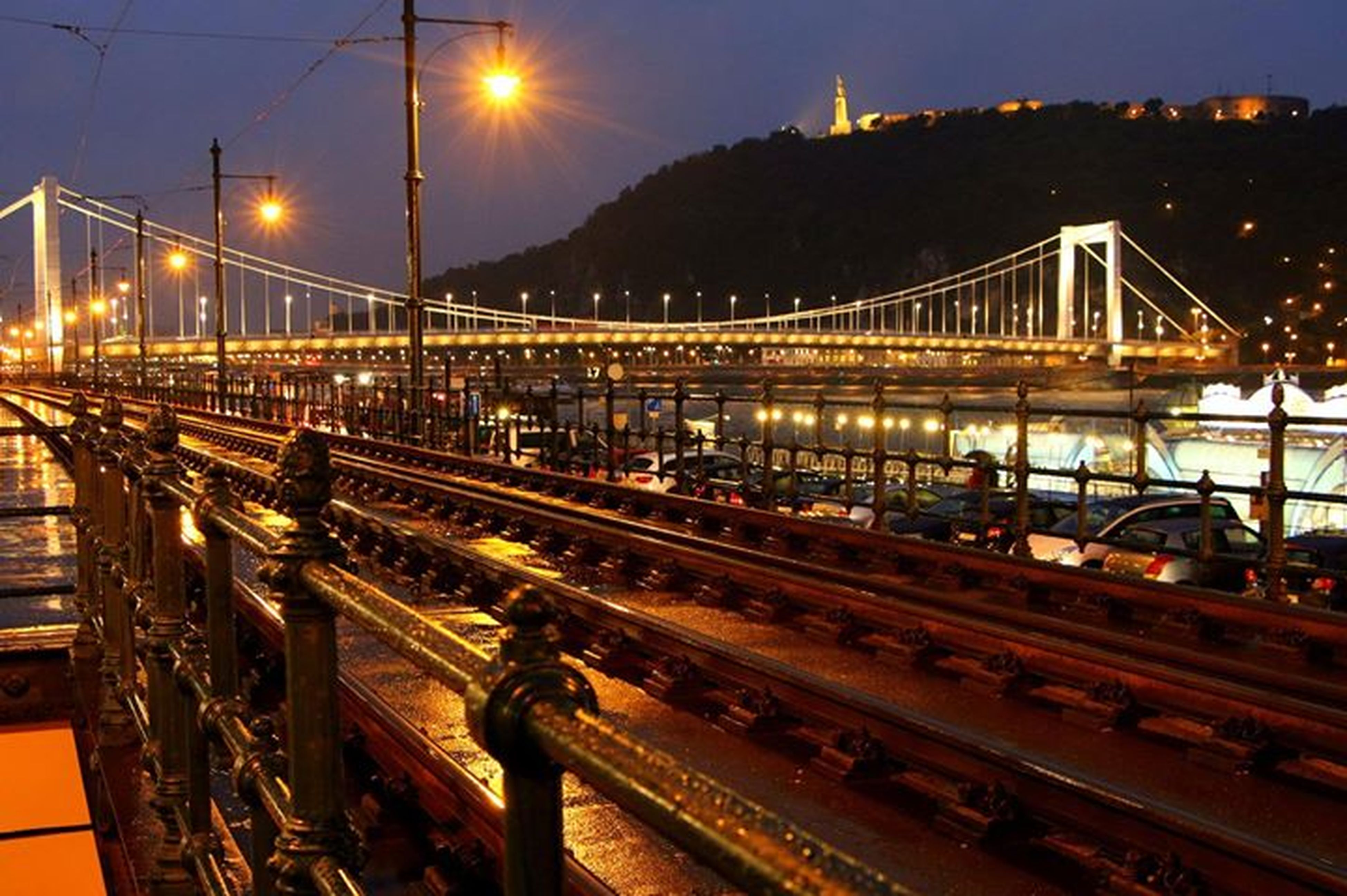 illuminated, transportation, night, street light, railroad track, mode of transport, built structure, rail transportation, public transportation, architecture, sky, connection, lighting equipment, bridge - man made structure, train - vehicle, city, outdoors, building exterior, land vehicle, travel