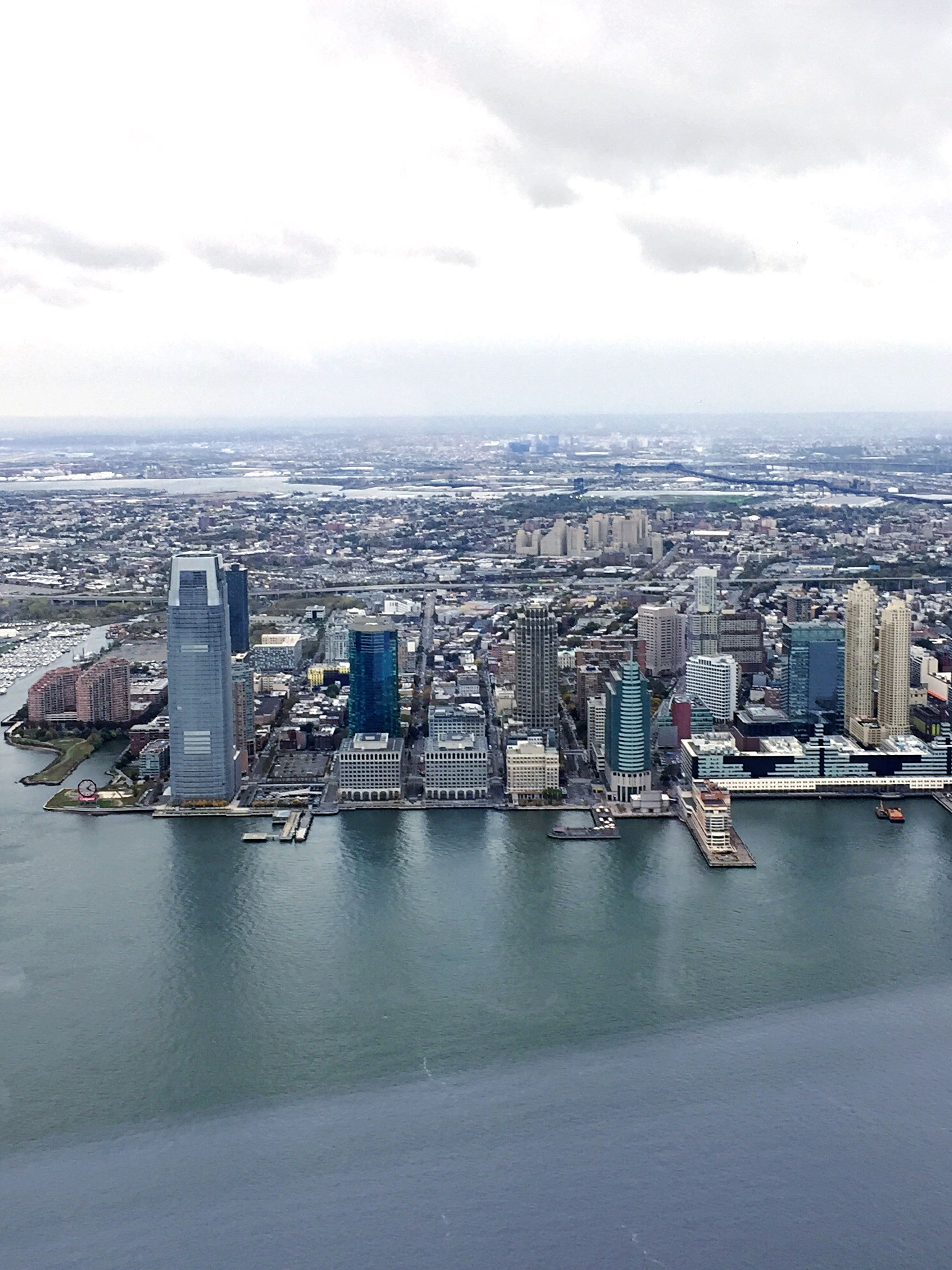 city, cityscape, architecture, building exterior, sky, built structure, cloud - sky, travel destinations, outdoors, city life, skyscraper, no people, urban skyline, modern, water, day, bridge - man made structure, downtown district