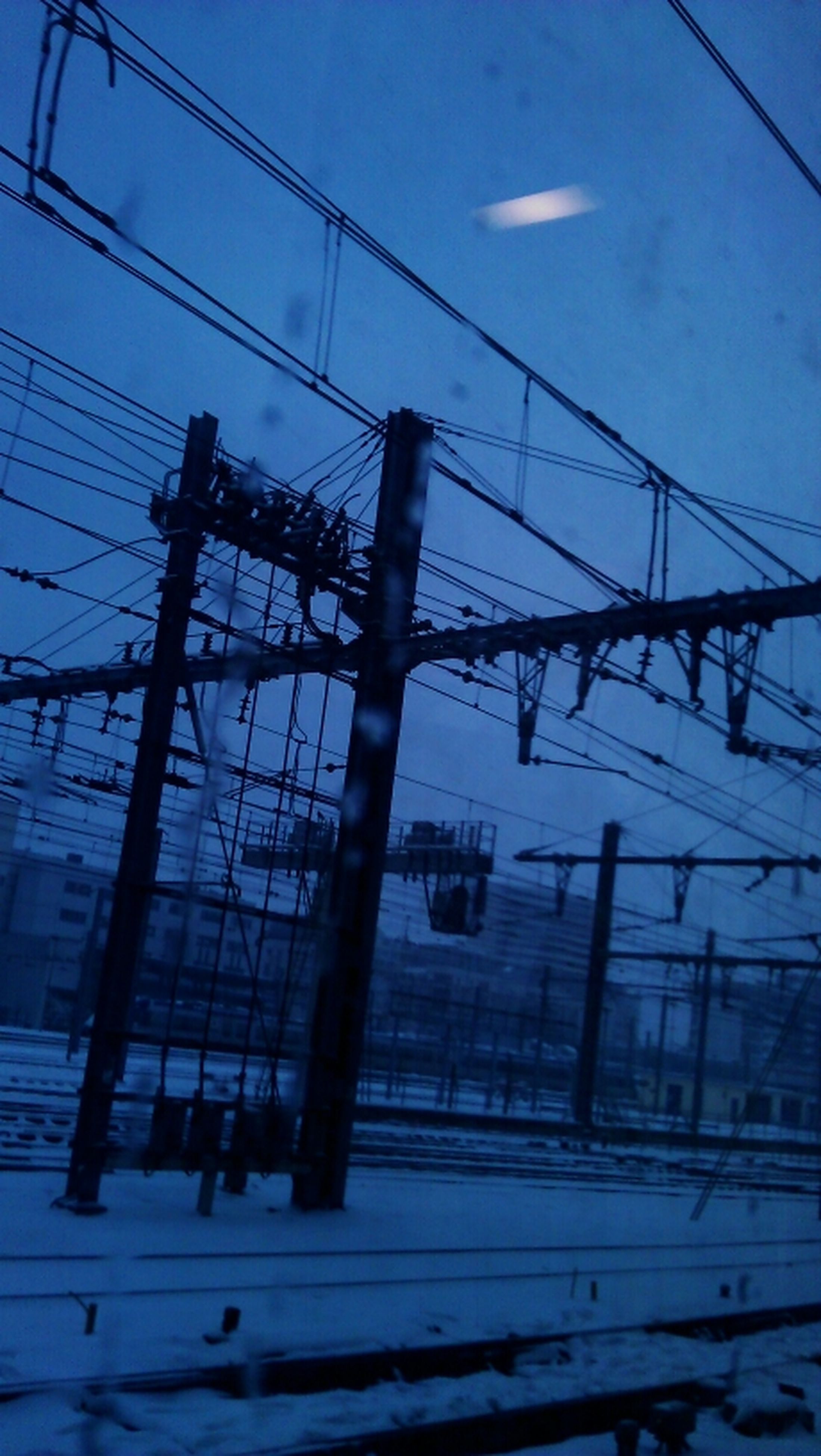 power line, power supply, electricity pylon, sky, electricity, cable, connection, low angle view, fuel and power generation, railroad track, blue, technology, built structure, transportation, no people, dusk, outdoors, cloud - sky, day, complexity