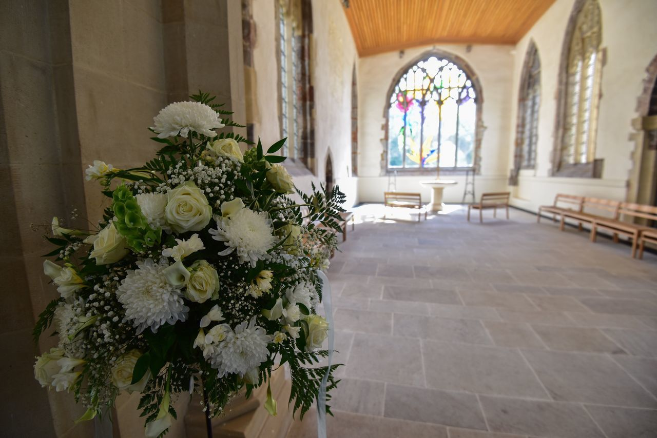 White Flowers Against Wall In Church