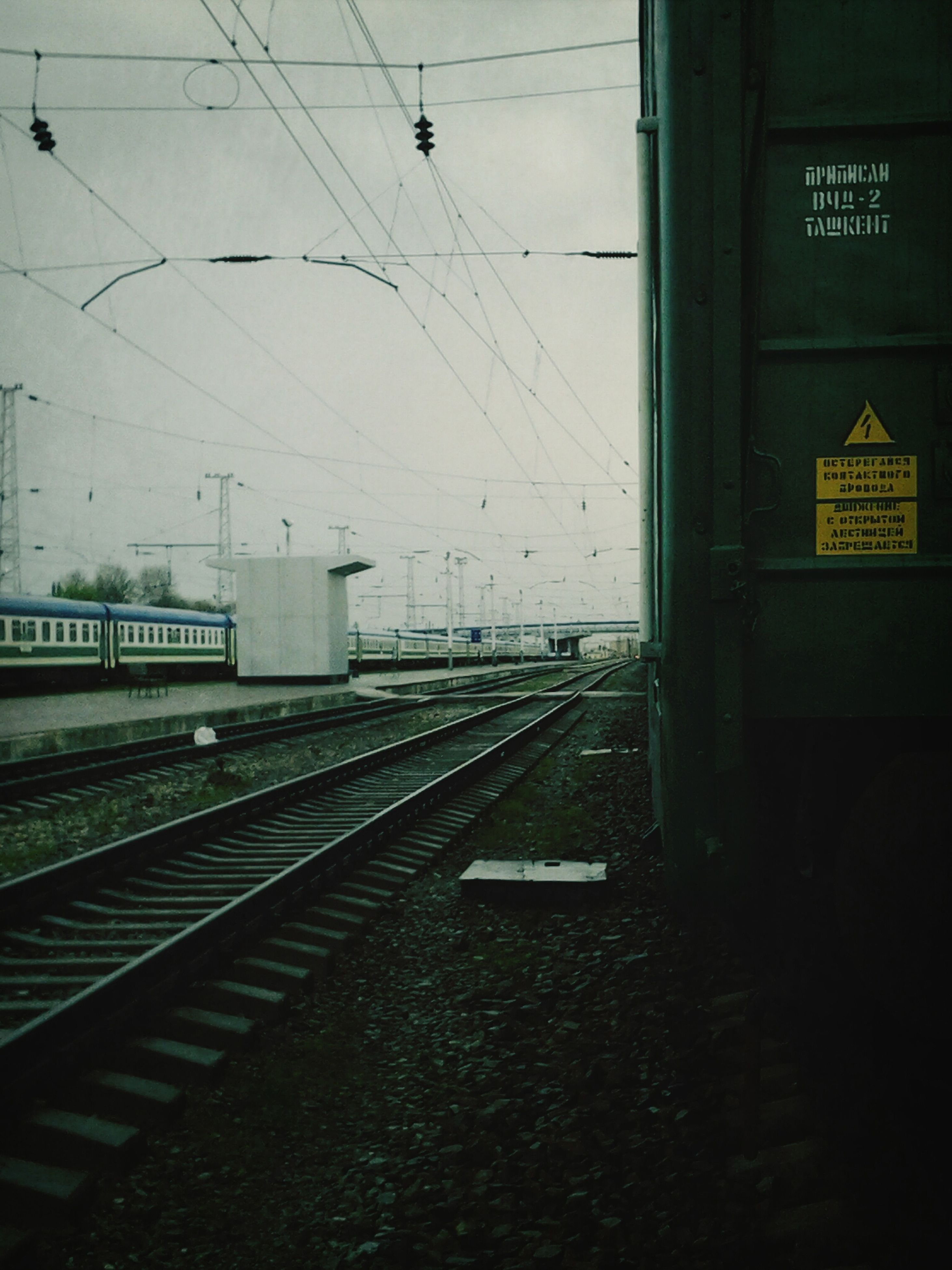 railroad track, transportation, rail transportation, public transportation, railroad station, the way forward, railroad station platform, diminishing perspective, built structure, architecture, power line, text, electricity, communication, electricity pylon, vanishing point, empty, train - vehicle, no people, day