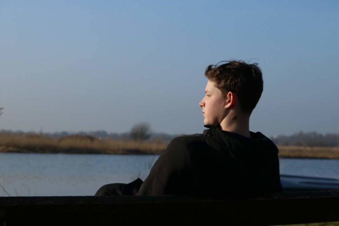 real people, one person, lake, lifestyles, boys, water, outdoors, leisure activity, sky, clear sky, nature, day, one teenage boy only, beauty in nature, young adult