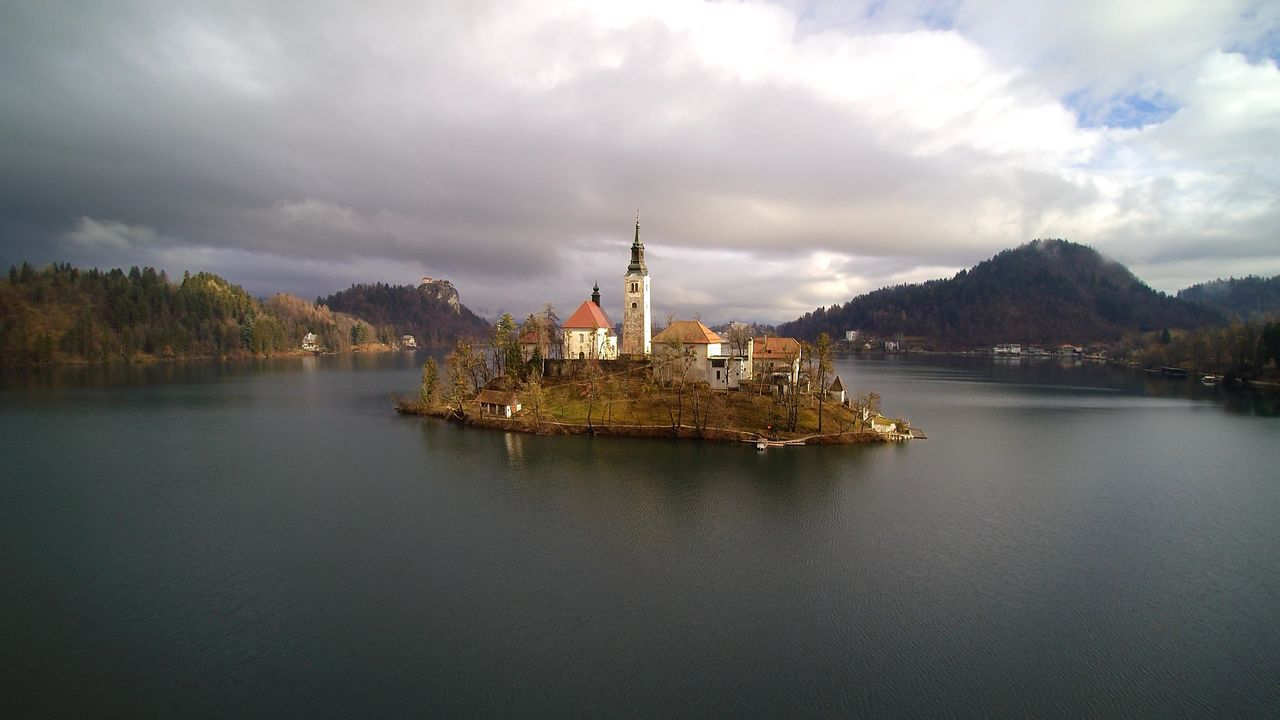 Scenic View Of Lake Bled Against Cloudy Sky