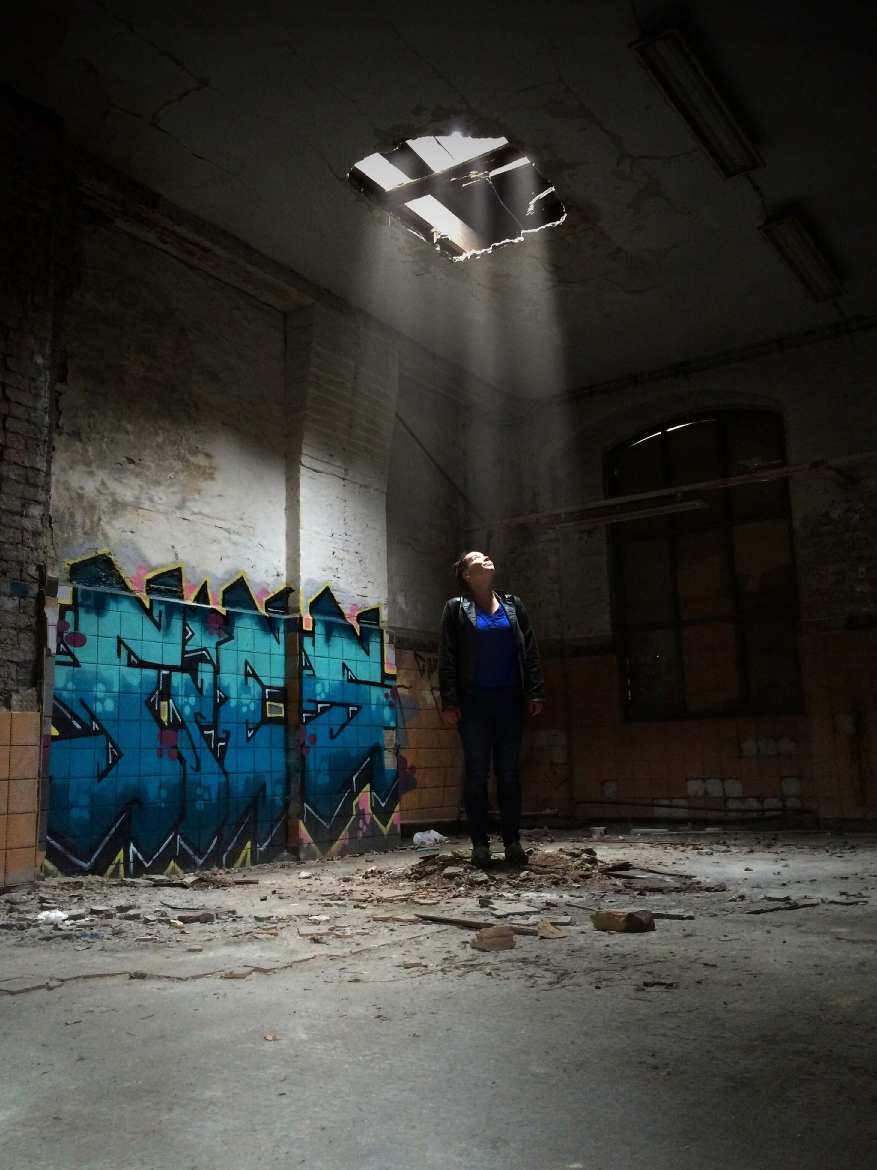 full length, indoors, built structure, architecture, rear view, abandoned, lifestyles, wall - building feature, casual clothing, graffiti, standing, men, leisure activity, messy, damaged, walking, flooring, person