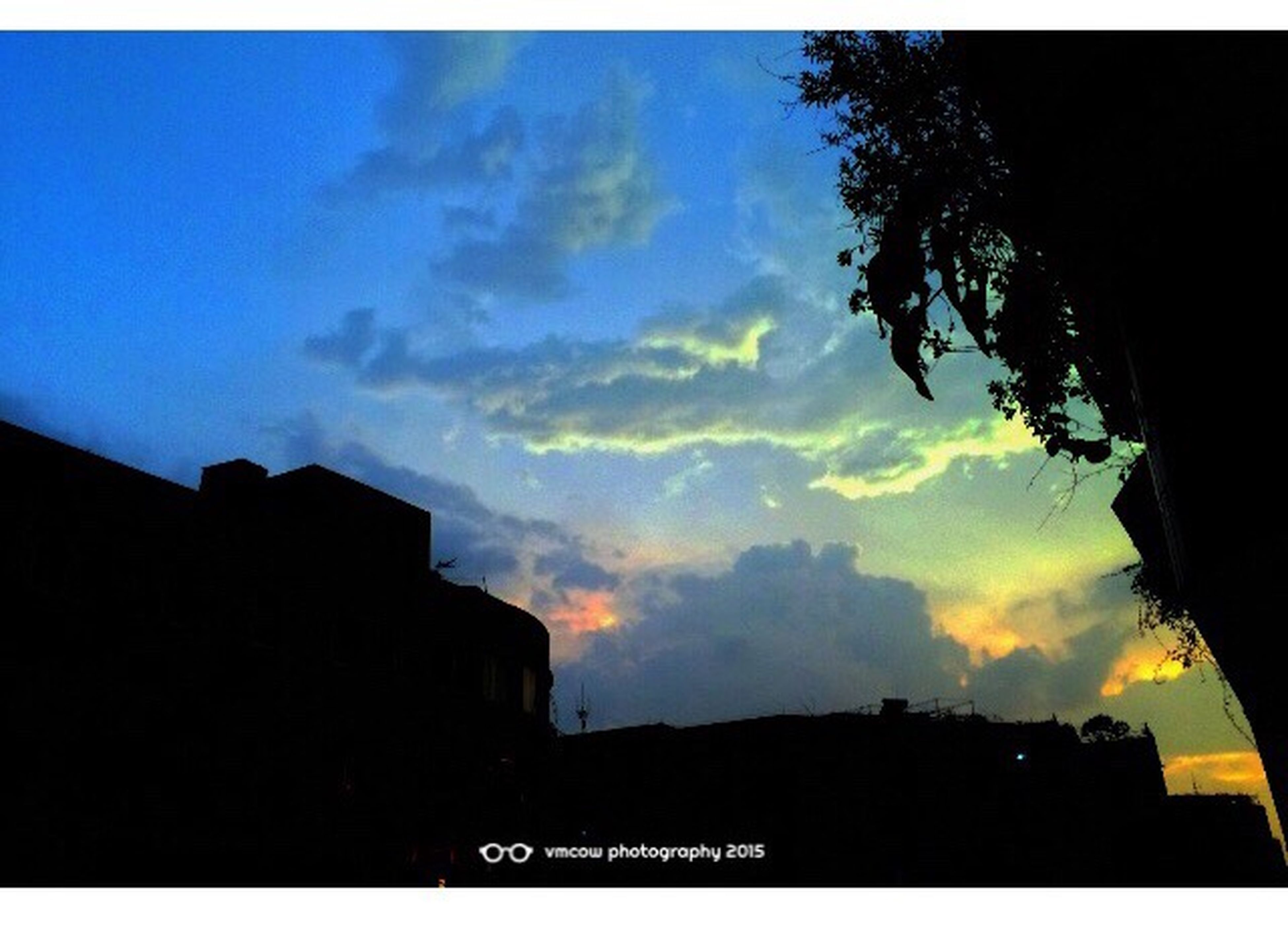 silhouette, sky, building exterior, low angle view, sunset, cloud - sky, built structure, tree, architecture, cloud, dusk, outdoors, nature, text, beauty in nature, communication, no people, cloudy, city, scenics