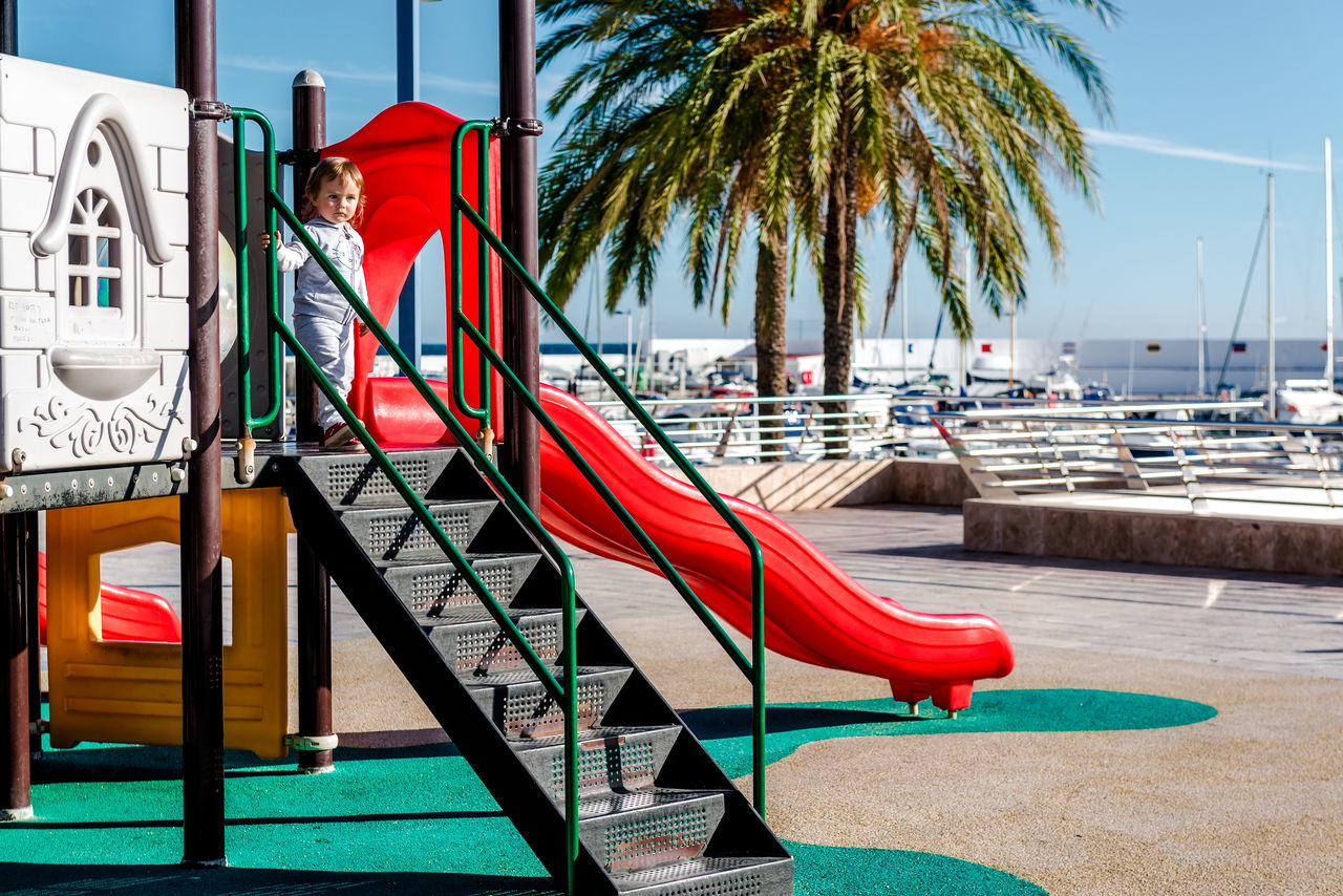 Baby girl on a playground Area Children Lifestyle Malaga Marbella Palm Tree SPAIN Amusement  Child Childhood Costa Del Sol Entertainment Leisure Leisure Activity Outdoors Playful Playground Recreational Pursuit Slide - Play Equipment Sunny Day Tourist Resort Tropical Climate