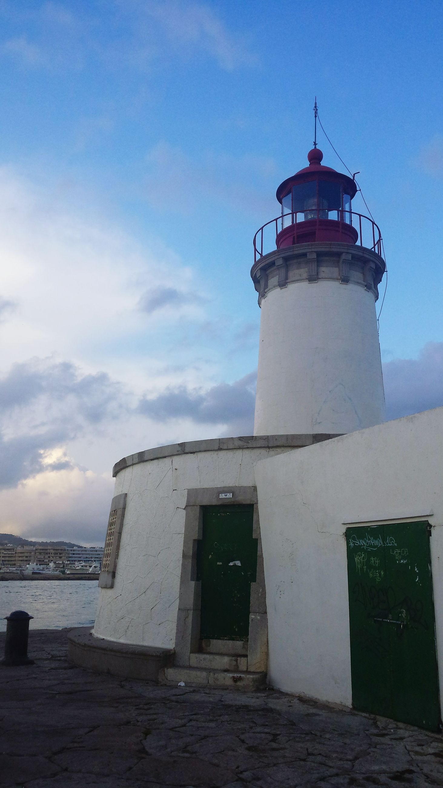 guidance, architecture, built structure, building exterior, lighthouse, direction, protection, safety, security, sea, low angle view, sky, tower, horizon over water, blue, water, outdoors, cloud - sky, surveillance, tall - high, weathered, no people, coastline, facade