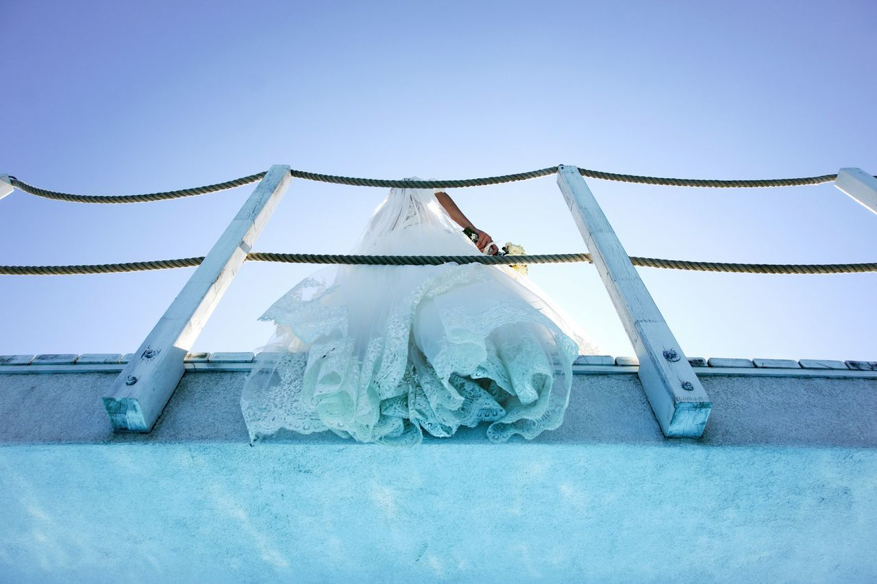 Low Angle View Of Bride Against Blue Sky
