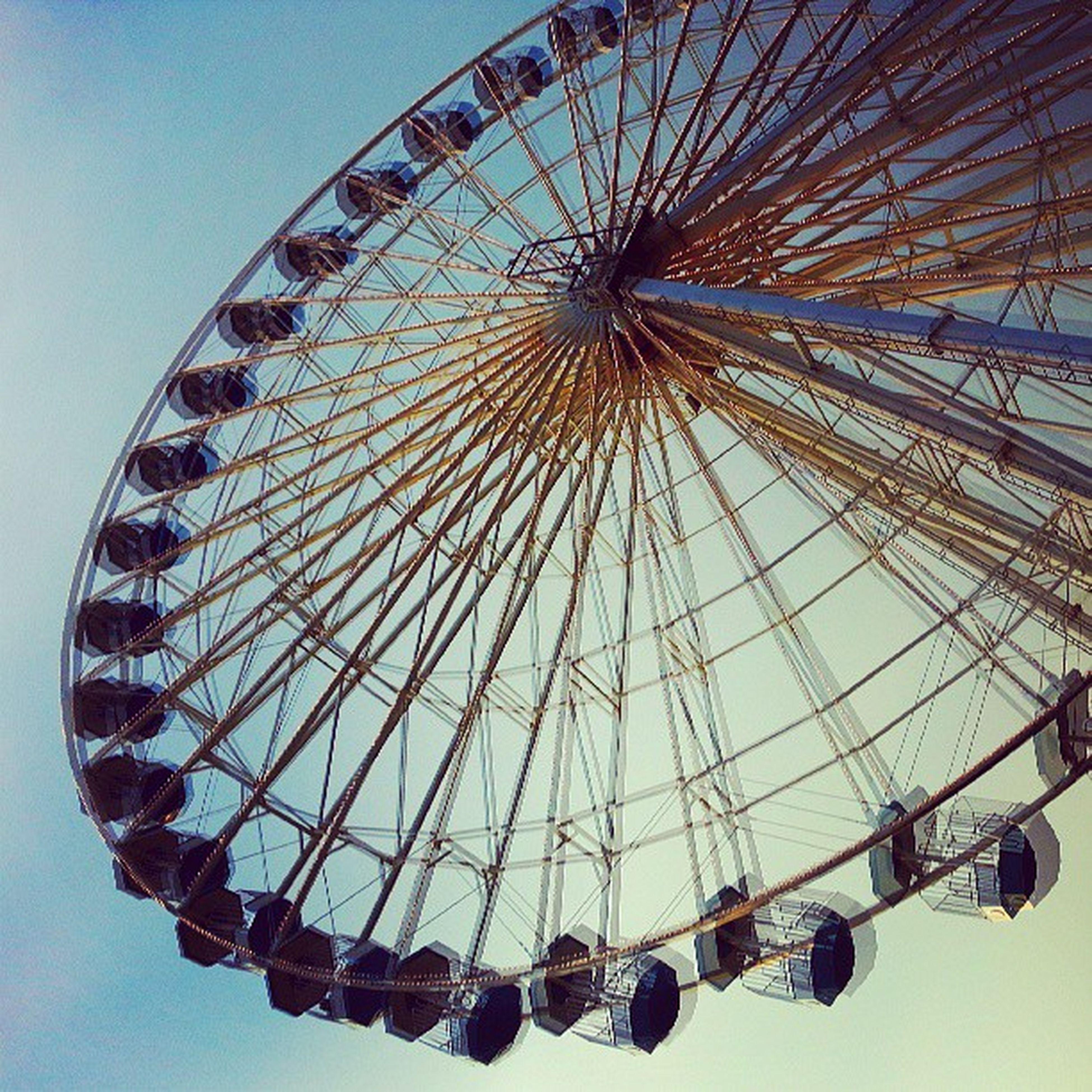 low angle view, amusement park ride, amusement park, ferris wheel, arts culture and entertainment, clear sky, built structure, sky, architecture, circle, pattern, fun, metal, day, blue, geometric shape, fairground ride, outdoors, design, no people