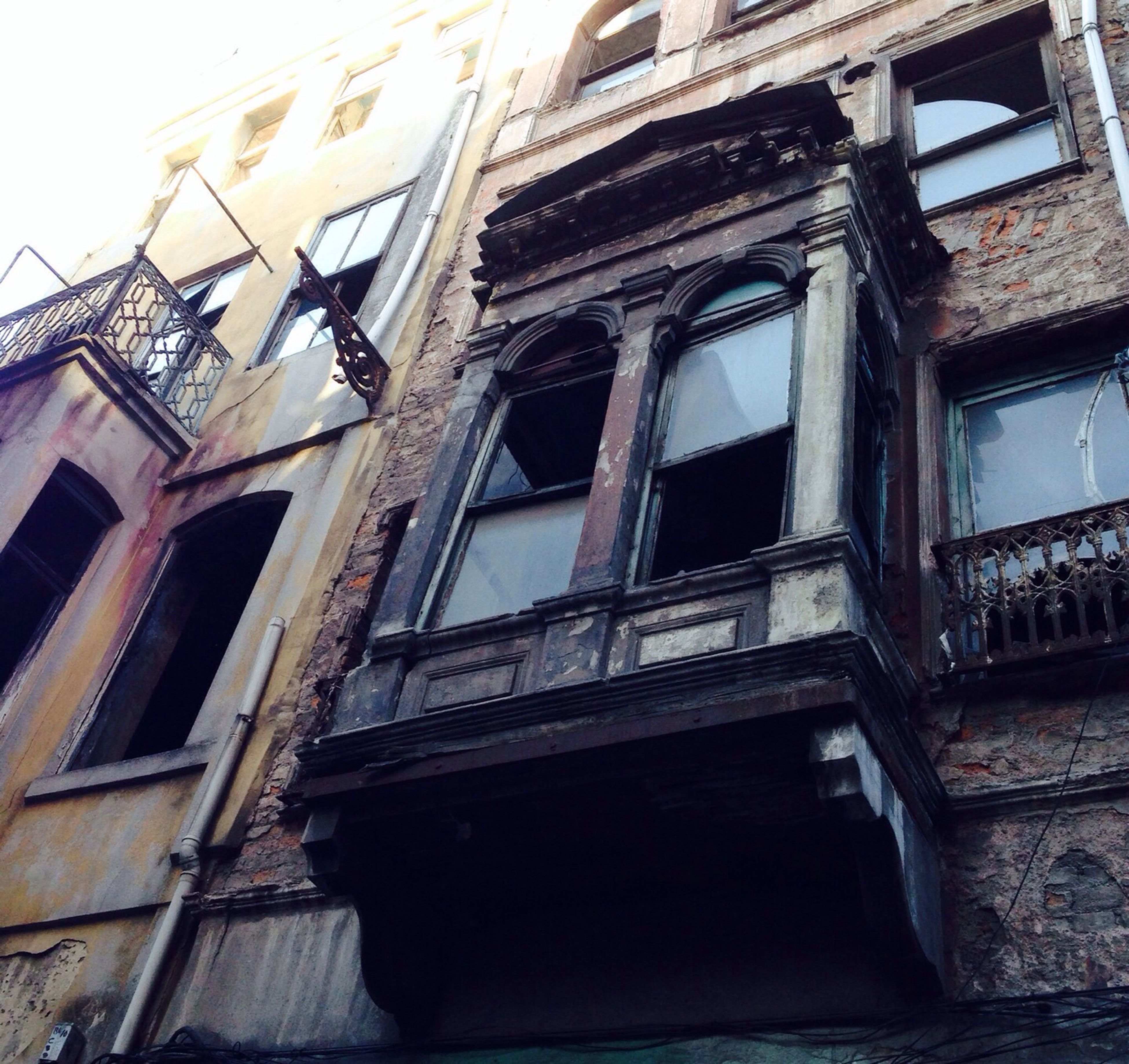 architecture, building exterior, built structure, low angle view, window, building, residential building, residential structure, old, abandoned, damaged, brick wall, house, weathered, obsolete, outdoors, day, no people, run-down, deterioration