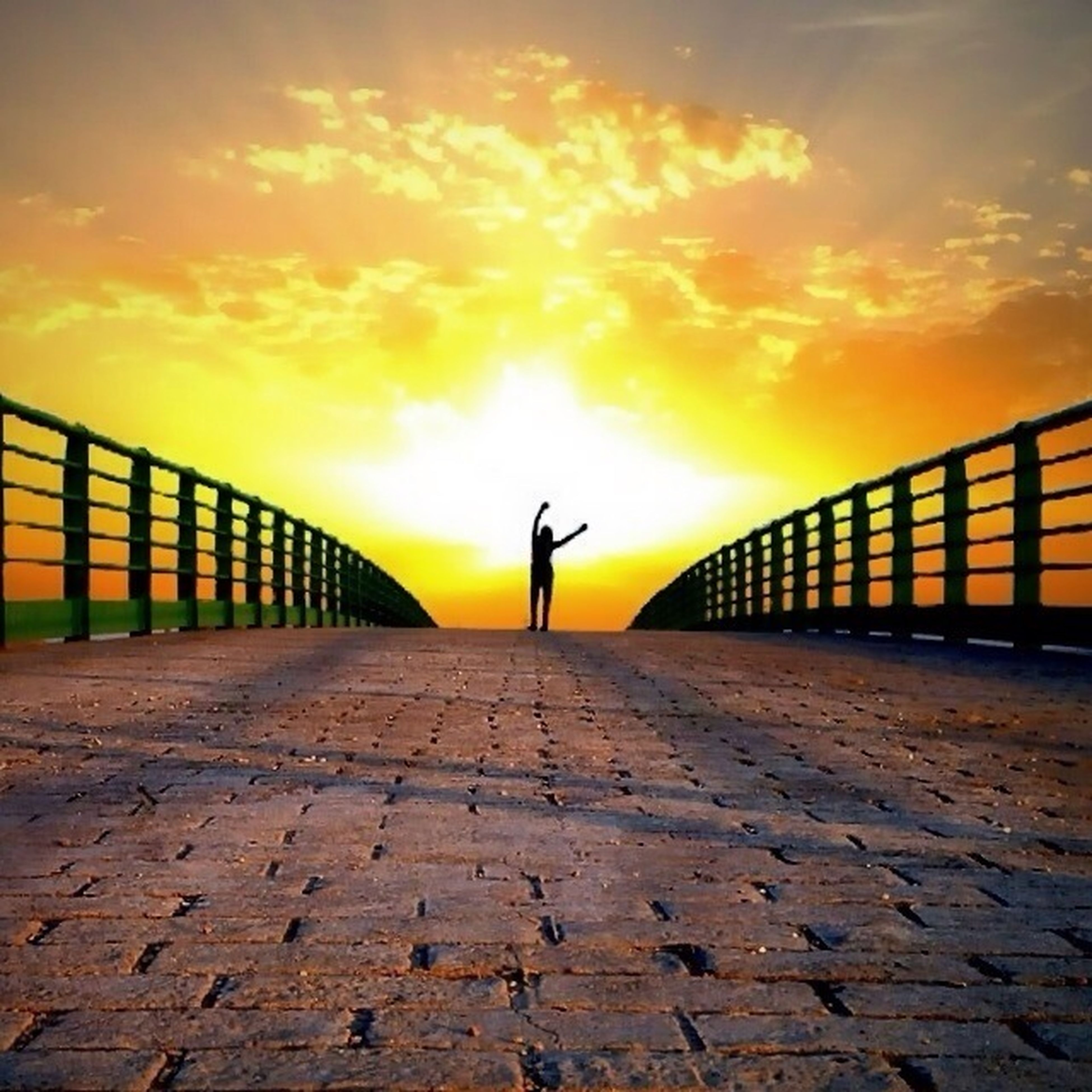 sunset, the way forward, sky, orange color, railing, cloud - sky, diminishing perspective, silhouette, full length, vanishing point, built structure, walking, transportation, sunlight, cloud, outdoors, lifestyles, nature