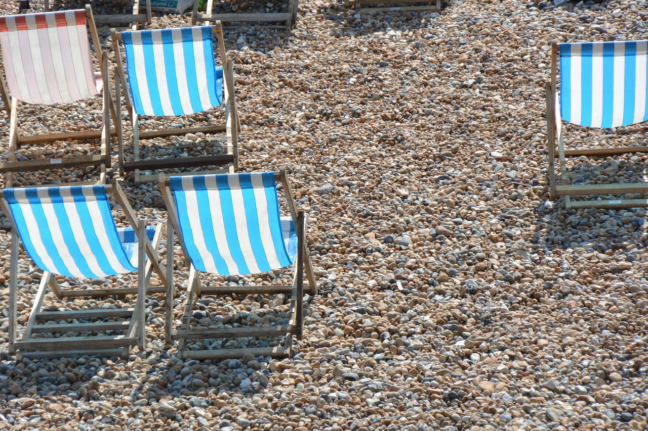 High Angle View Of Empty Deck Chairs On Sunny Day At Beach