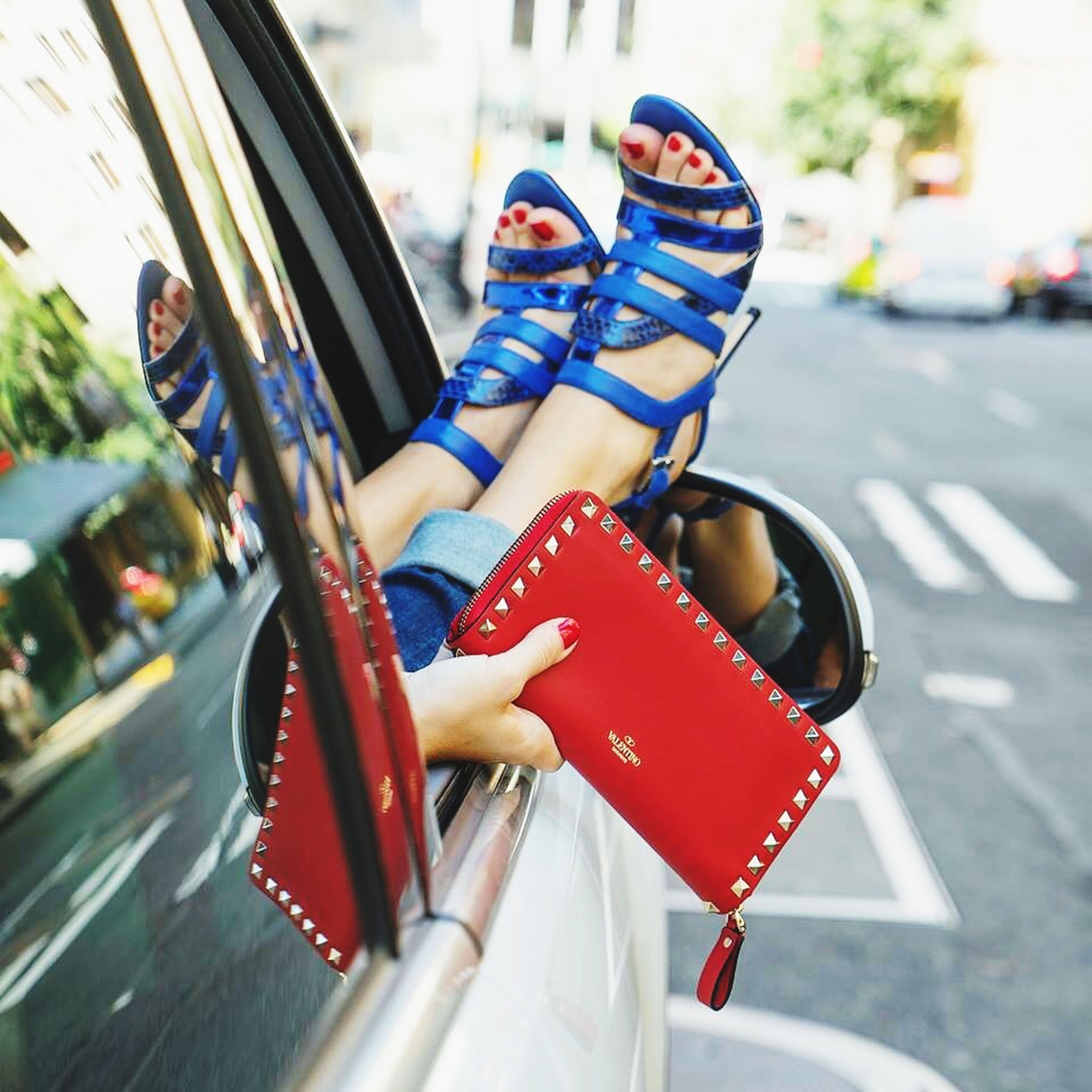 red, focus on foreground, shoe, transportation, street, close-up, footwear, low section, day, mode of transport, outdoors, sunlight, road, fashion, land vehicle, person, selective focus, multi colored