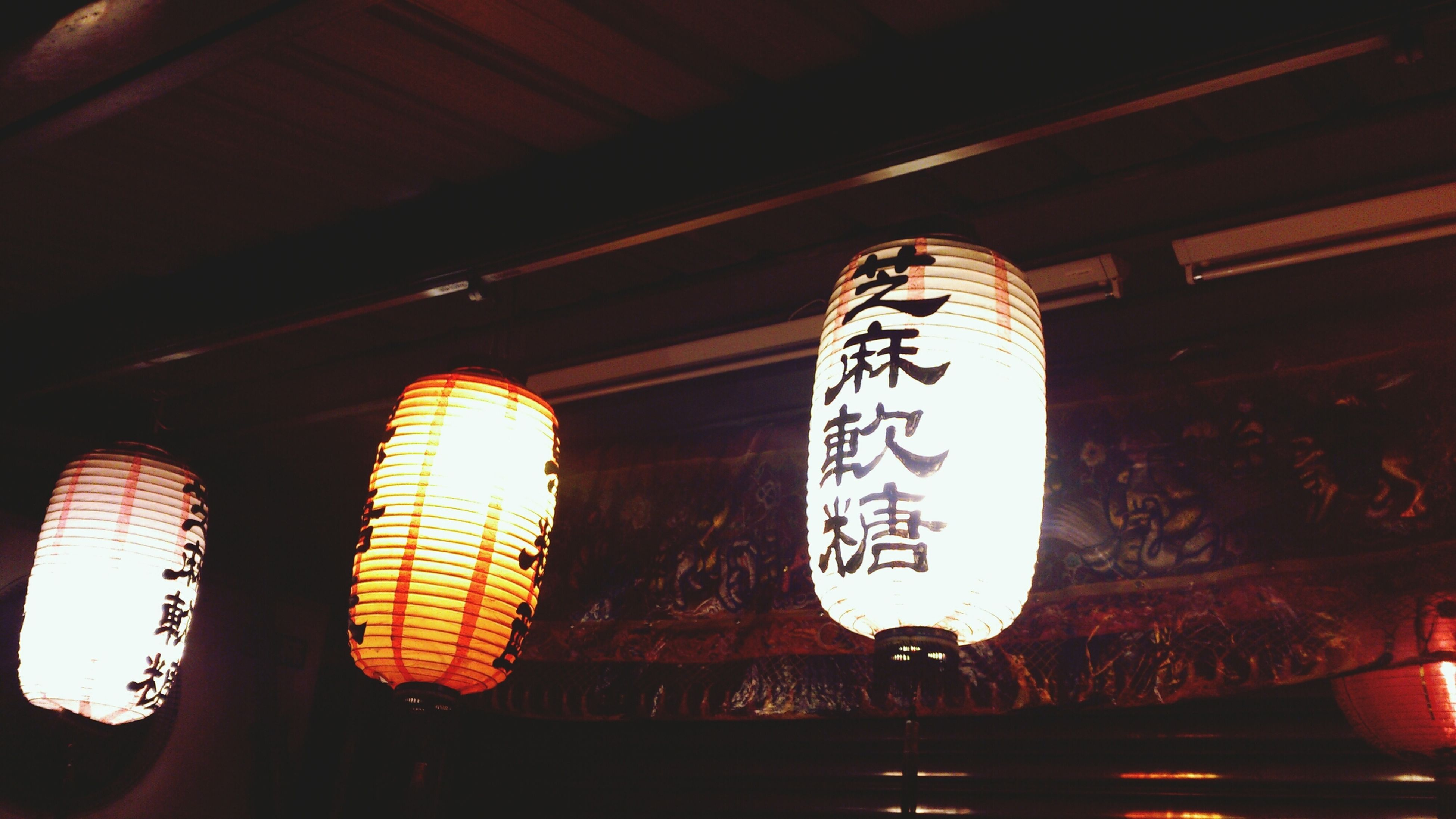 indoors, illuminated, text, lighting equipment, western script, communication, low angle view, red, close-up, night, no people, hanging, light - natural phenomenon, lantern, wall - building feature, glowing, decoration, pattern, dark, home interior