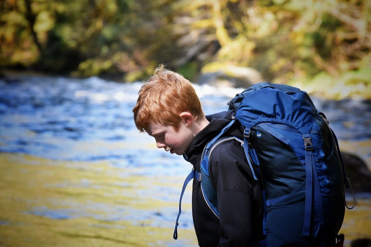 Real People One Person Backpack Leisure Activity Focus On Foreground Jacket Outdoors Side View Casual Clothing Young Adult Day Nature Blond Hair Lifestyles Young Men Standing Boys Water Hiking Adventure Photography Themes Weekend Activities Memories Hiking