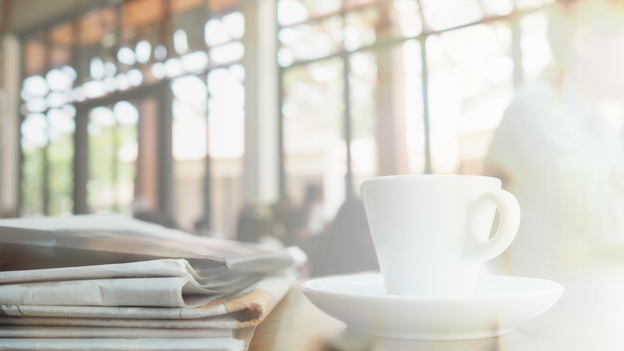 Cup of espresso coffee with newspaper in coffee shop background, blurred focus Break The Mold Breakfast Business Coffee - Drink Coffee Cup Coffee Shop Coffee Time Day Focus On Foreground Food And Drink Freshness Indoors  Morning Light Newspaper Relaxing Saucer Startup Table