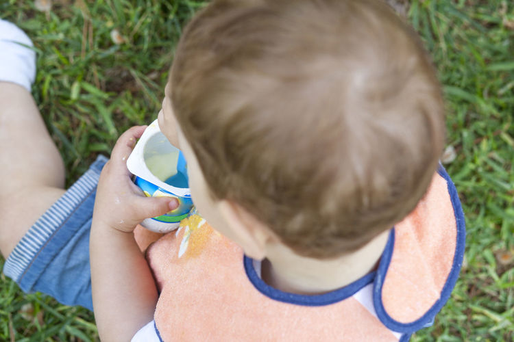 2 year-old boy eating a yoghurt sitting on the grass. Overhead shot Bonding Boys Child Childhood Close-up Day Elementary Age Family With One Child Grass Headshot Lifestyles Moisturizer Outdoors People Real People Rear View Skin Care Summer Togetherness