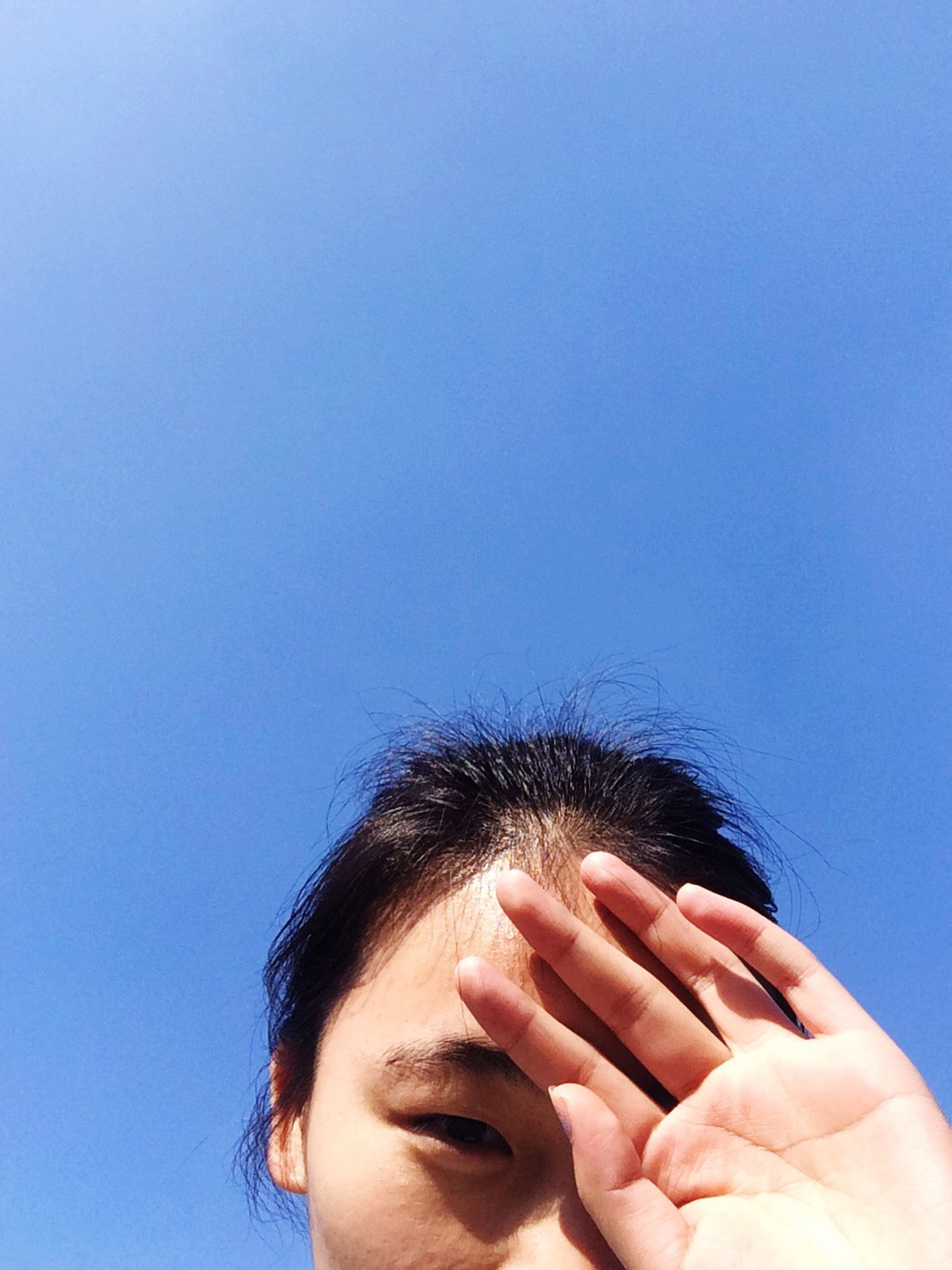 person, copy space, studio shot, white background, lifestyles, part of, close-up, headshot, cropped, clear sky, holding, leisure activity, human finger, blue, front view, human face, unrecognizable person