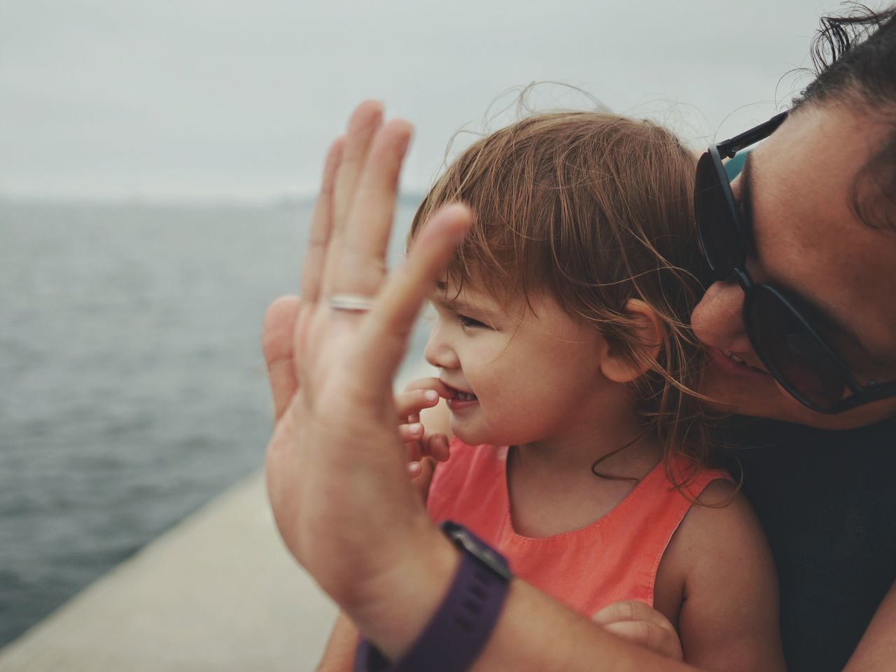 waving goodbye. focus on foreground Tranquility human face person Children goodbyes Saying goodbye Motherhood water ocean