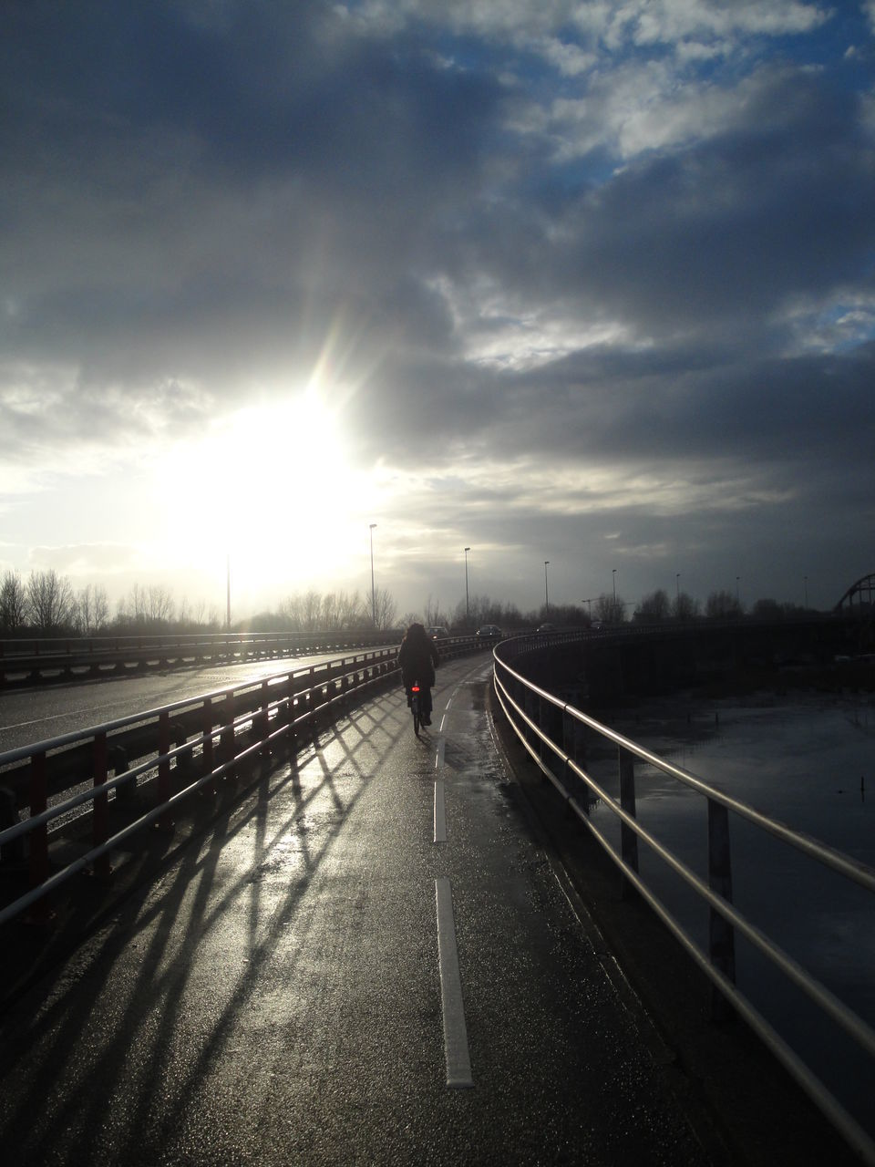 bridge - man made structure, railing, transportation, cloud - sky, sunset, sky, river, suspension bridge, connection, full length, city, one person, architecture, outdoors, built structure, the way forward, motion, road, travel destinations, women, water, nature, day, people