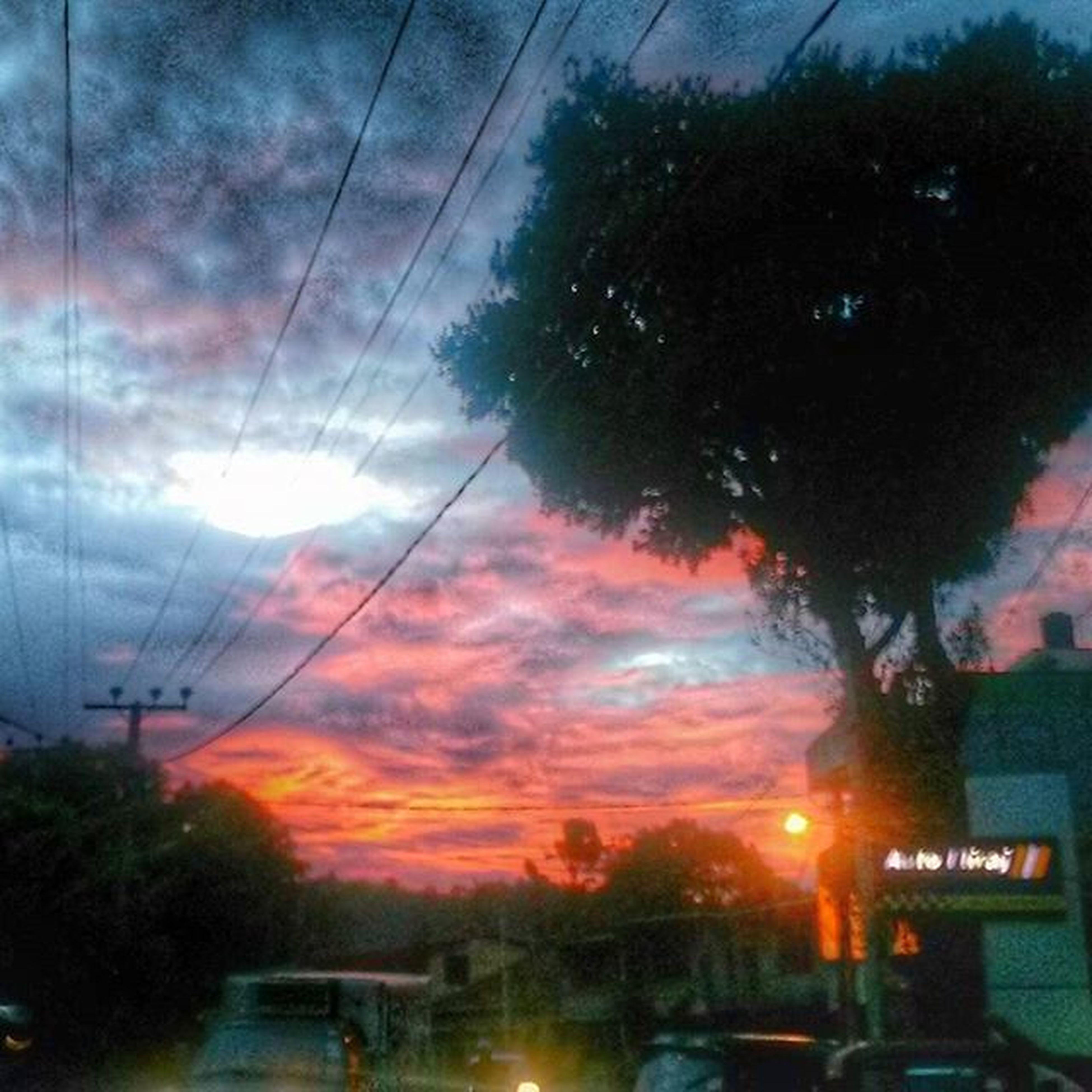 sunset, transportation, car, sky, land vehicle, mode of transport, cloud - sky, tree, road, silhouette, orange color, street, cloudy, power line, street light, cloud, nature, beauty in nature, electricity pylon, scenics