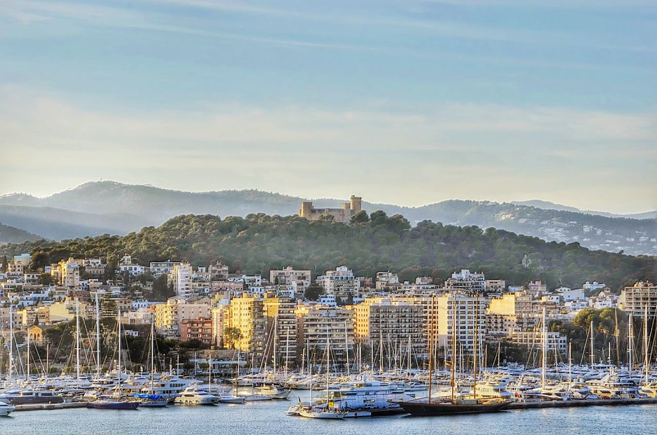mountain, nautical vessel, water, architecture, building exterior, mode of transport, built structure, no people, house, sky, transportation, outdoors, residential building, day, waterfront, moored, travel destinations, tree, harbor, mountain range, cityscape, nature, city, sea, yacht