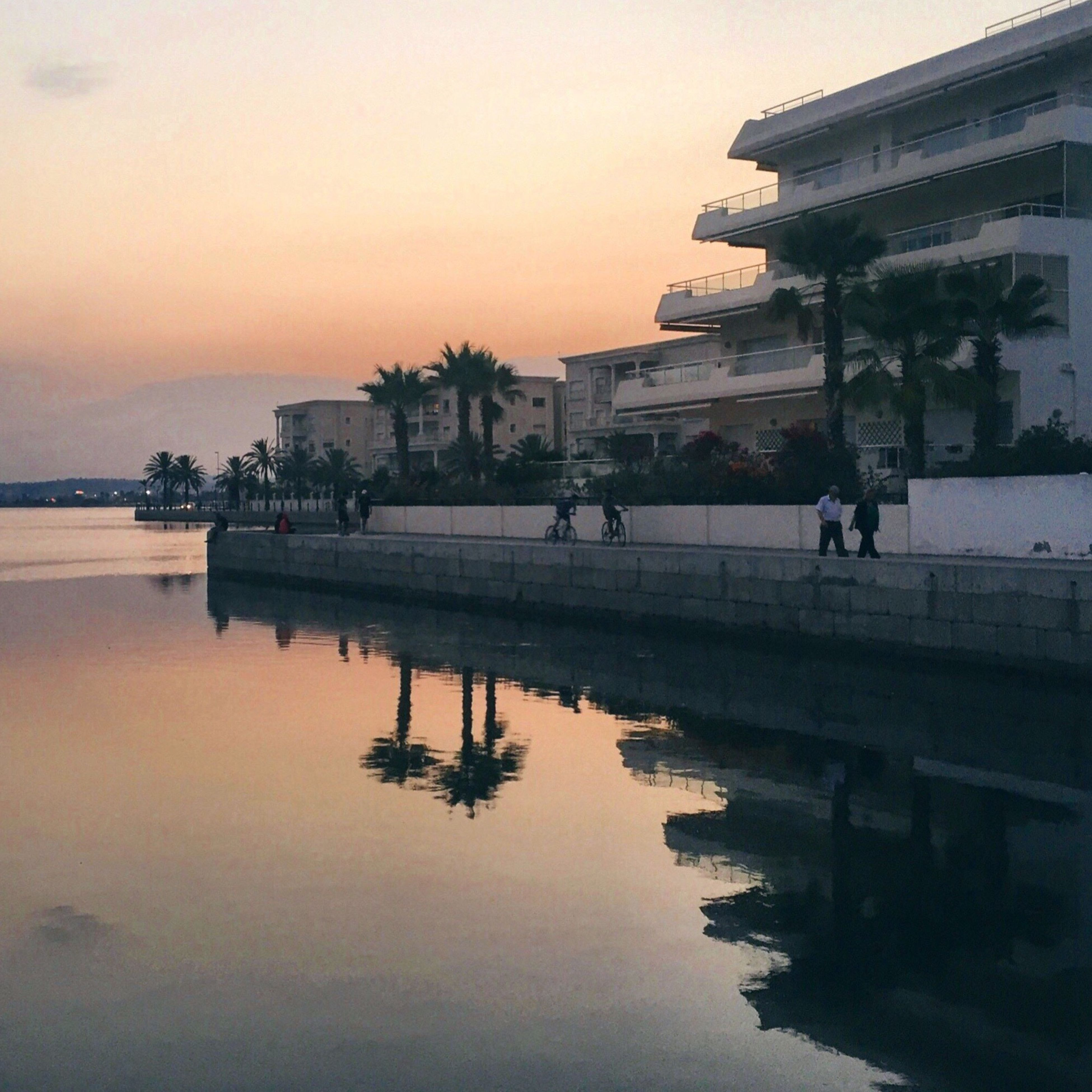 architecture, built structure, building exterior, sunset, water, large group of people, person, men, lifestyles, dusk, leisure activity, orange color, sky, group of people, city life, tourism, vacations, outdoors, waterfront, history, tranquility, scenics