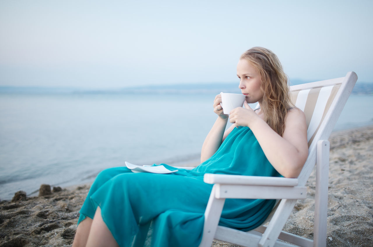 Thoughtful Woman Drinking Coffee While Sitting On Lounge Chair At Sea Shore
