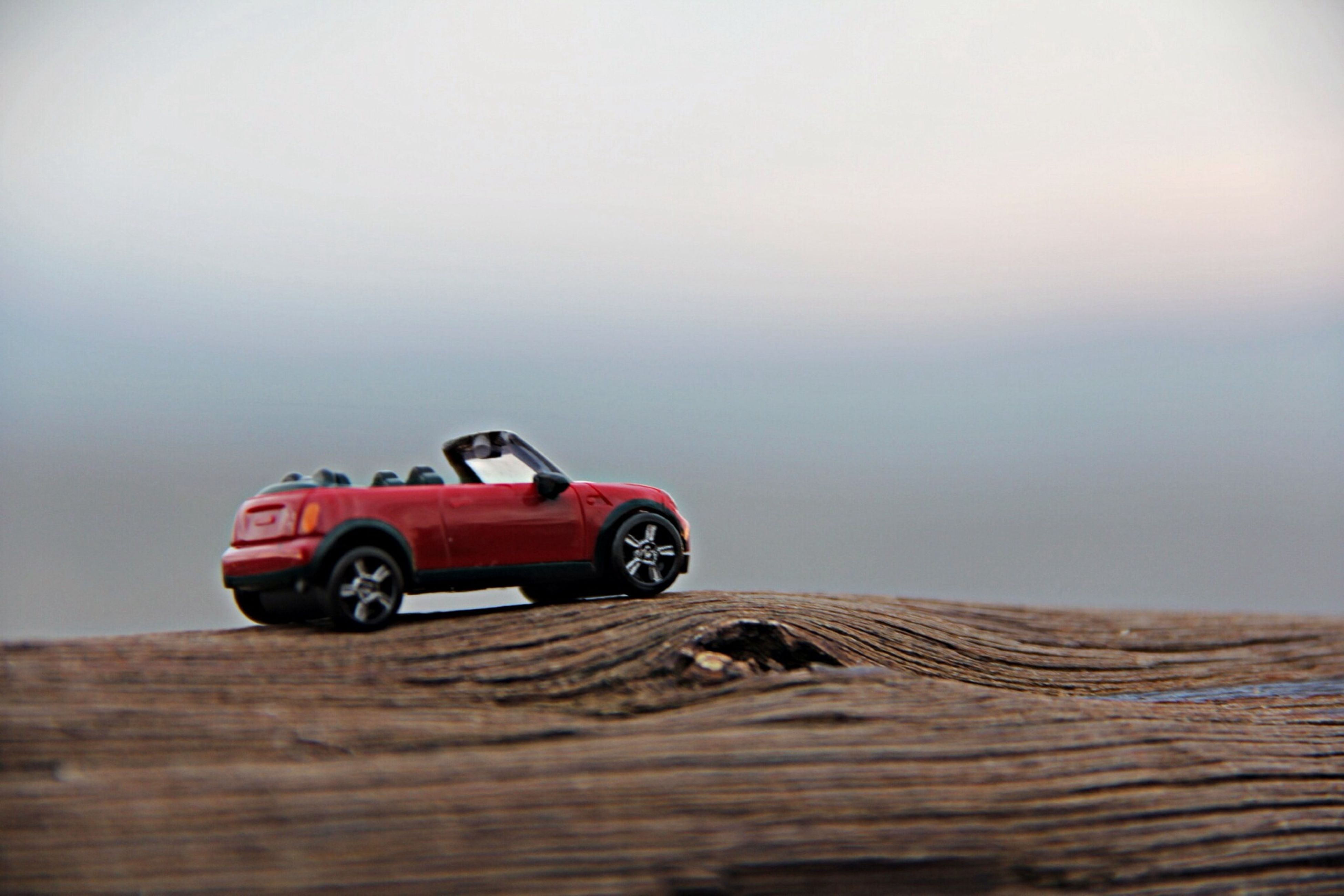 wood - material, transportation, sky, selective focus, land vehicle, clear sky, mode of transport, day, focus on foreground, wooden, car, nature, sand, tranquility, outdoors, tranquil scene, wood, copy space, surface level, travel