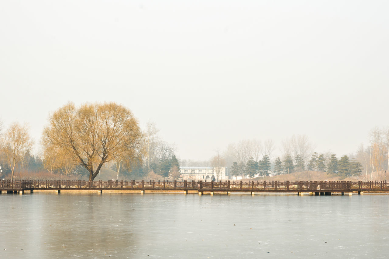 architecture, built structure, water, tree, river, bare tree, copy space, outdoors, building exterior, waterfront, day, nature, tranquility, winter, no people, scenics, travel destinations, cold temperature, clear sky, sky, beauty in nature, city