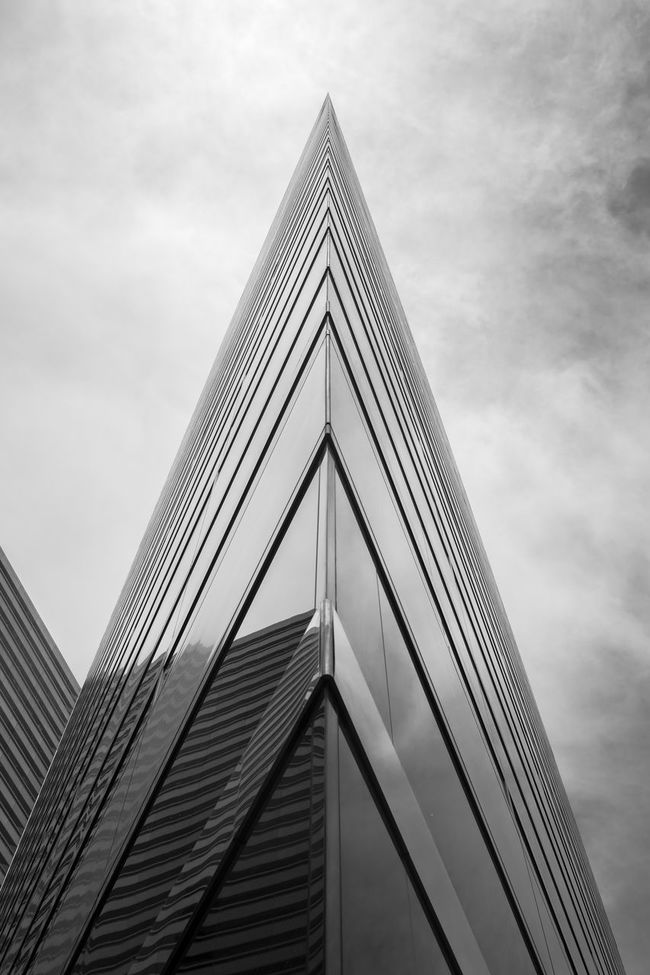 Abstract of a corner of a modern building pointing to cloudy sky; in black and white. Abstract Architecture Artistic Black And White Blackandwhite Building Exterior Built Structure City Cloud Colors Design LINE Low Angle View Material Modern Office Building Pattern Pierce Sharp Sky Skyscraper Stab Tower Triangle