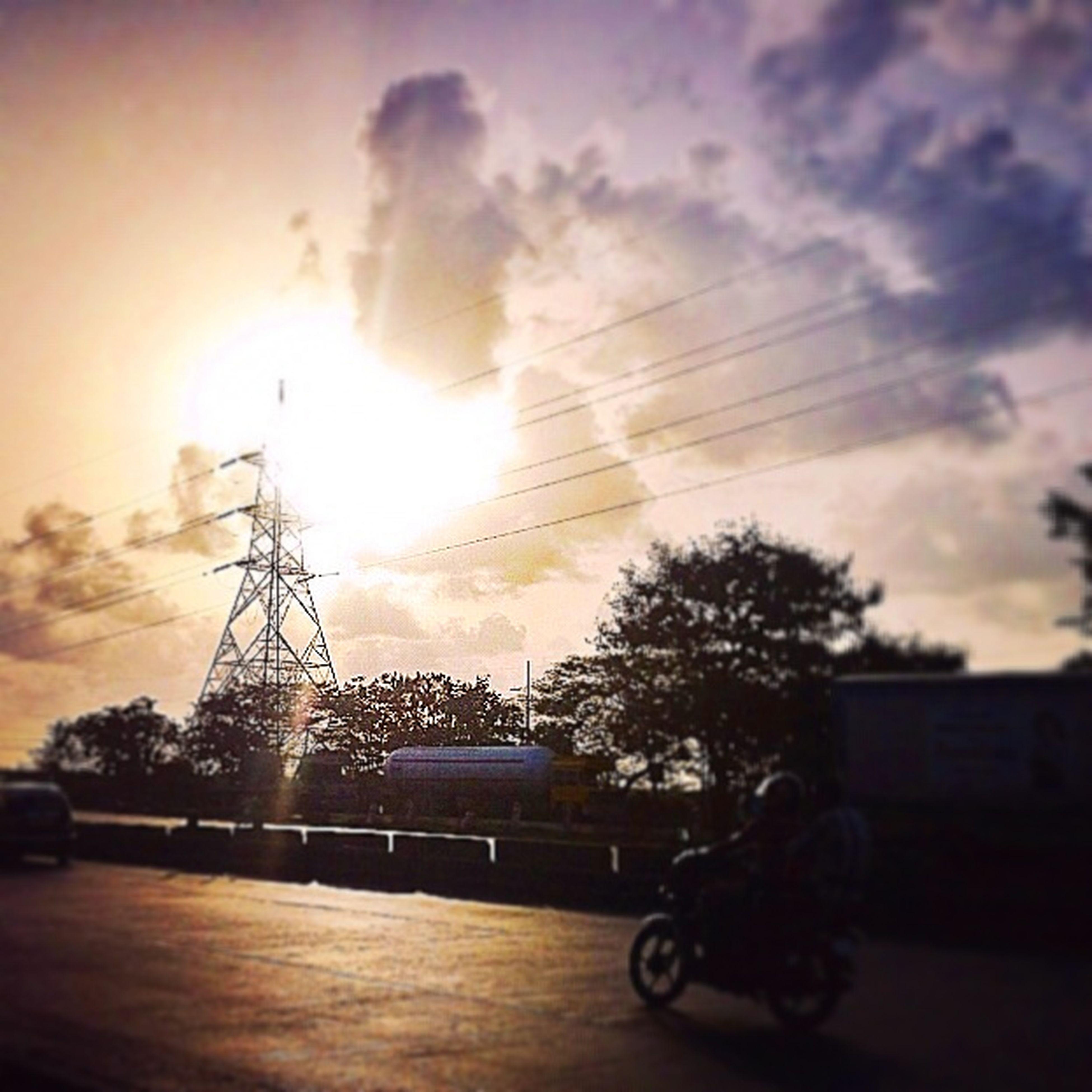 bicycle, sunset, land vehicle, transportation, sky, built structure, mode of transport, silhouette, architecture, building exterior, street, cloud - sky, sunlight, sun, city, road, orange color, outdoors, railing