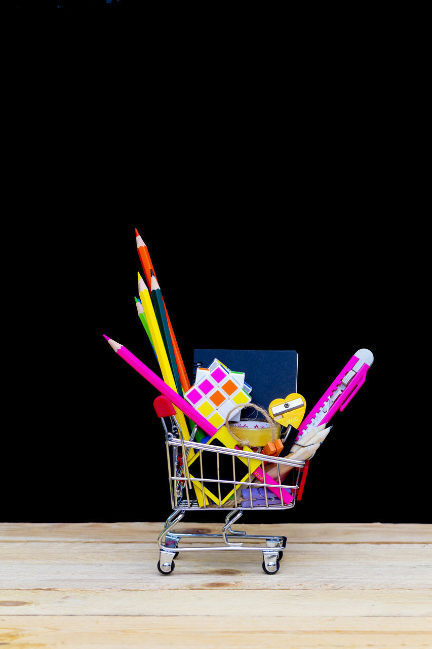 studio shot, black background, multi colored, no people, large group of objects, indoors, desk organizer, close-up, day