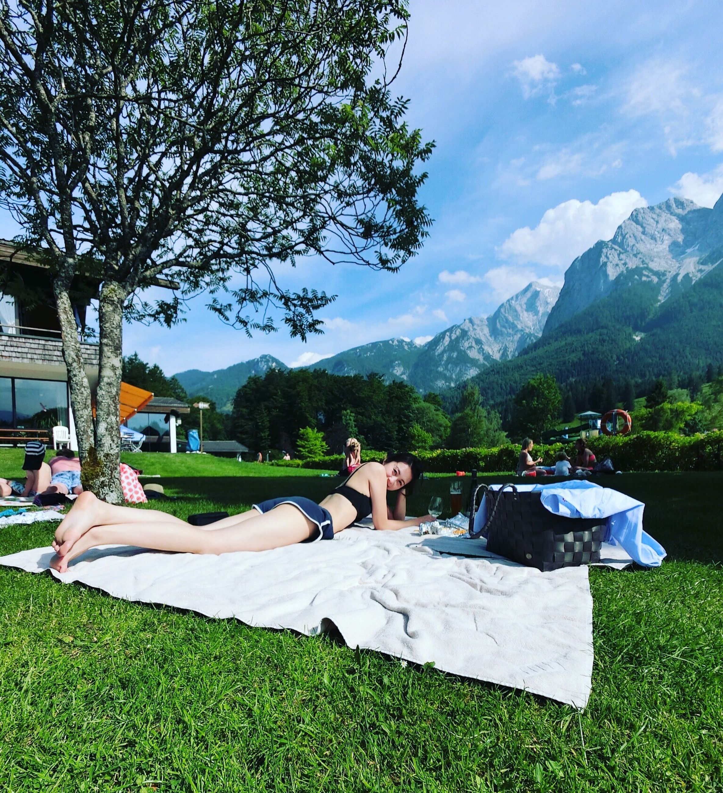 lying down, lying on back, tree, relaxation, grass, low section, day, leisure activity, outdoors, real people, sky, one person, nature, barefoot, full length, human leg, mountain, lifestyles, sunlight, women, men, beauty in nature, wireless technology, young adult, people
