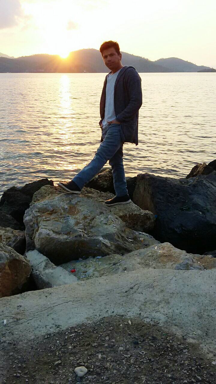 water, full length, rock - object, one person, sunset, real people, sea, young men, lifestyles, nature, casual clothing, standing, young adult, men, leisure activity, tranquil scene, looking at camera, scenics, beauty in nature, outdoors, portrait, beach, handsome, relaxation, sky, sitting, one man only, day, only men, adult, adults only, people