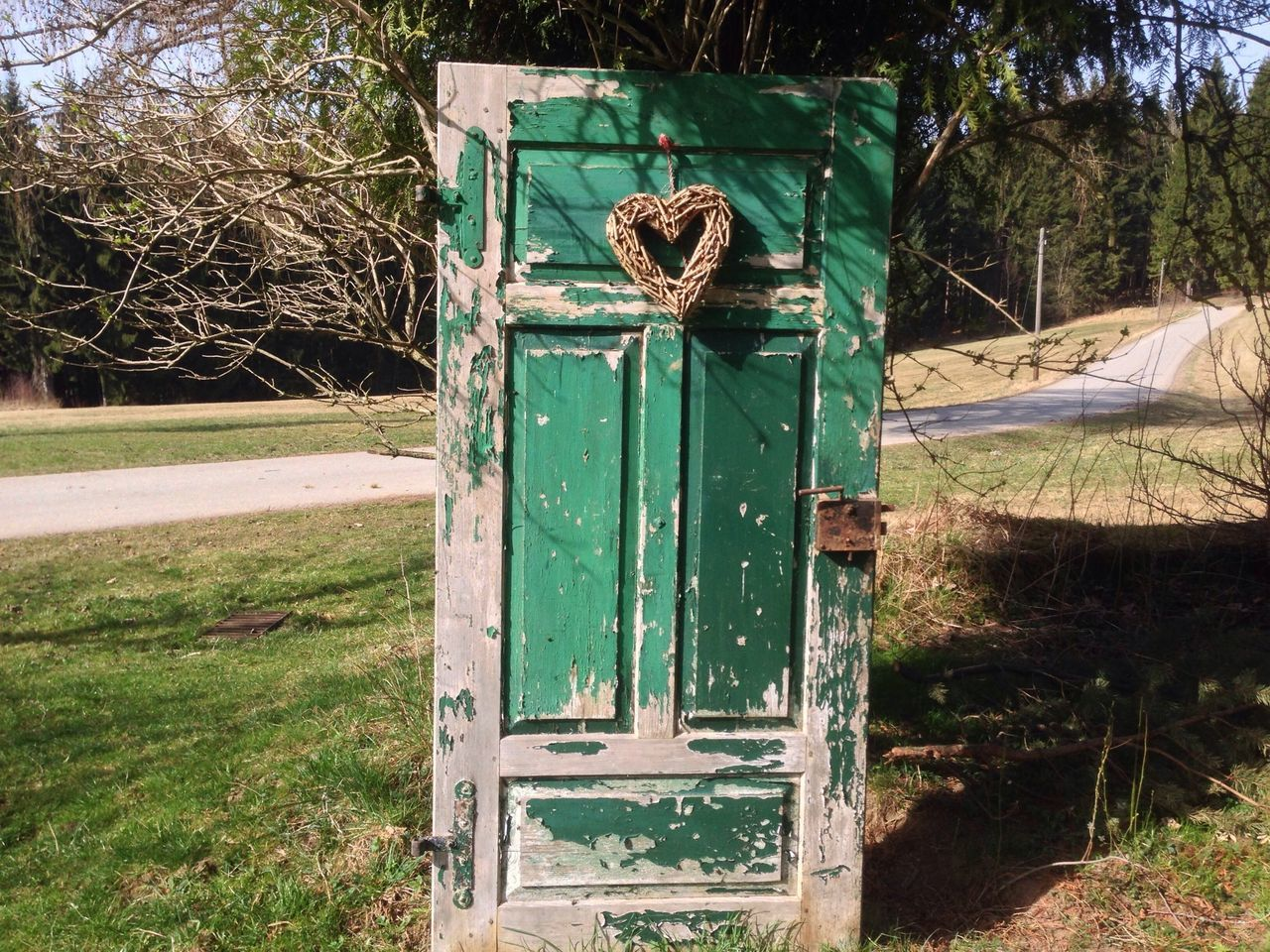 Abandoned Door With Heart On Grassy Field