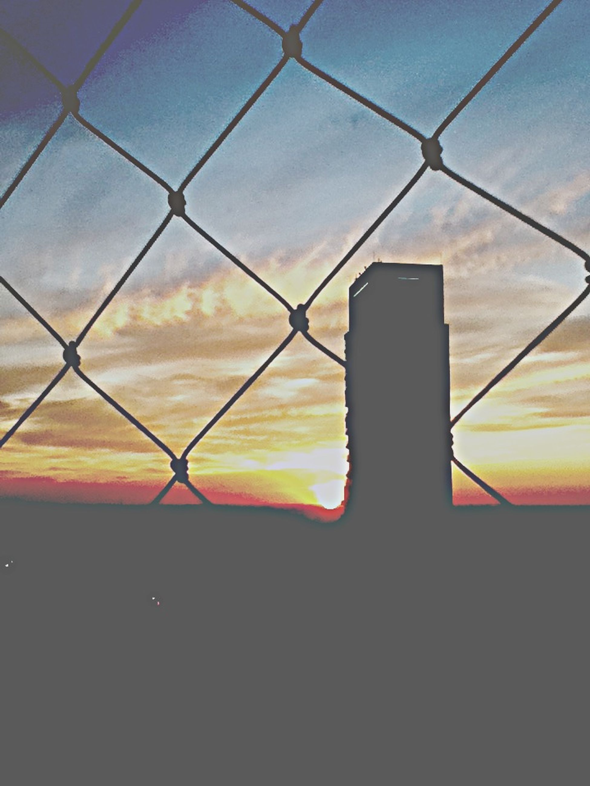 sunset, sky, safety, protection, cloud - sky, orange color, security, silhouette, metal, no people, cloud, chainlink fence, built structure, window, outdoors, fence, architecture, backgrounds, pattern, dusk