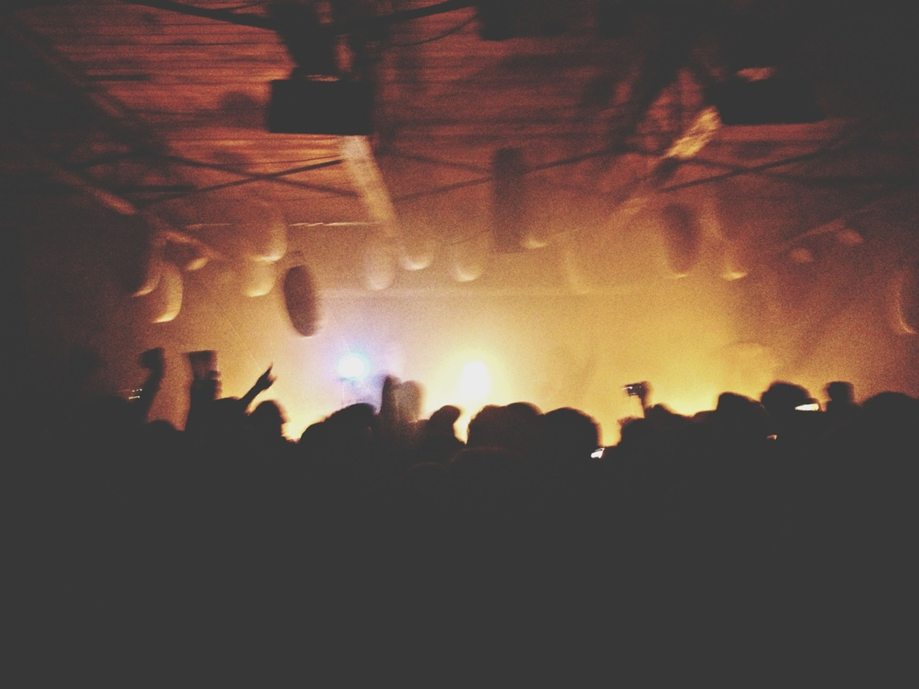 large group of people, illuminated, night, silhouette, crowd, men, lifestyles, leisure activity, arts culture and entertainment, light - natural phenomenon, enjoyment, celebration, event, indoors, person, nightlife, performance, fun