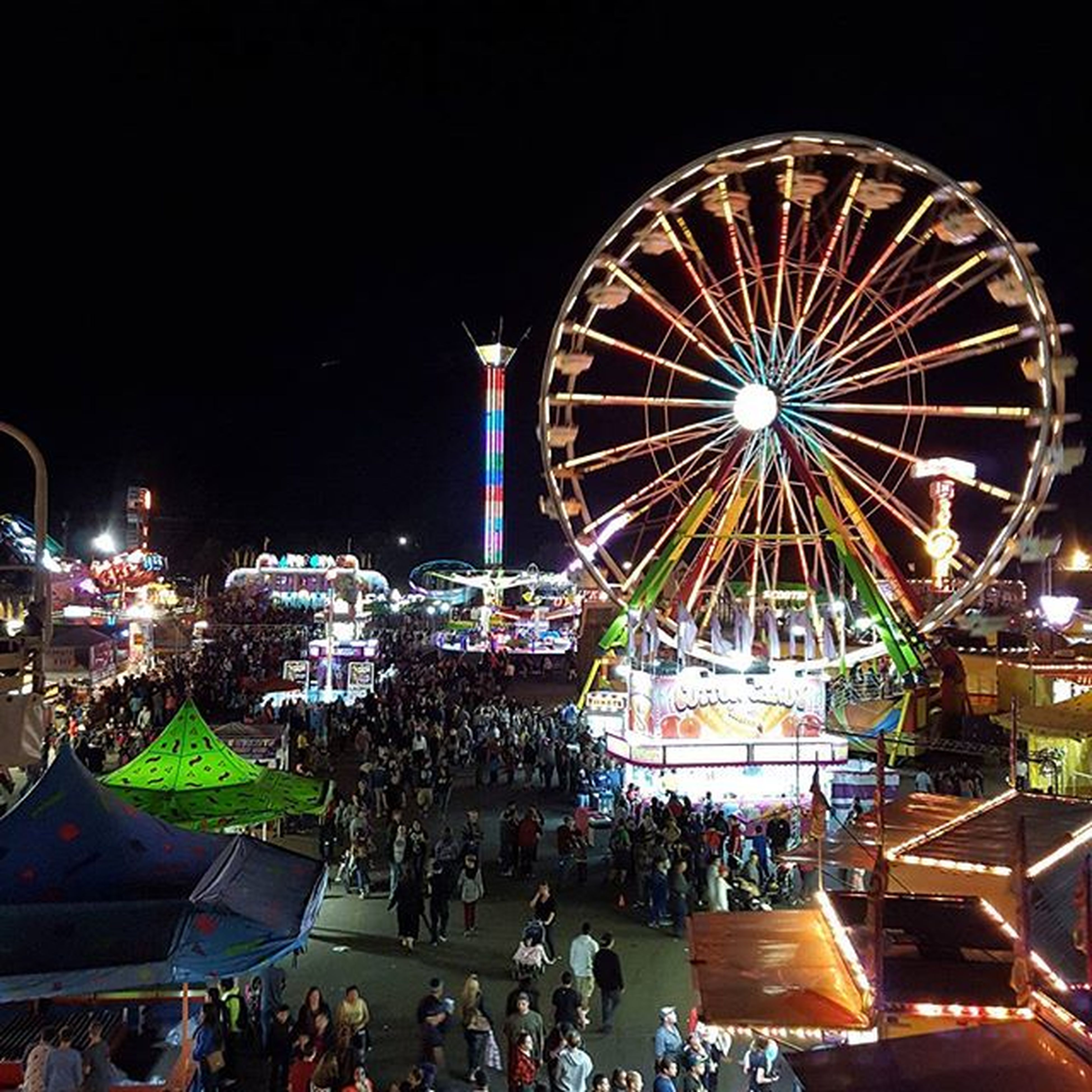 illuminated, night, arts culture and entertainment, amusement park, amusement park ride, ferris wheel, large group of people, lighting equipment, sky, fun, enjoyment, leisure activity, built structure, celebration, architecture, outdoors, multi colored, incidental people, clear sky